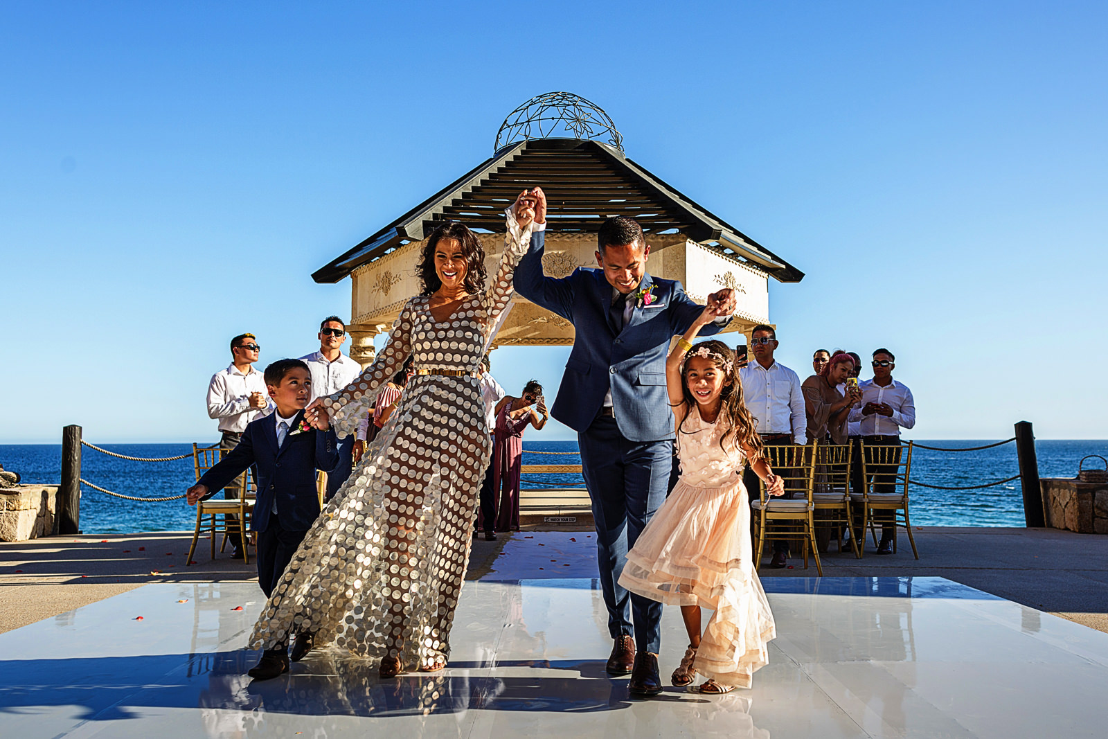 Groom, bride and kids raising arms at the end of the destination wedding ceremony at Grand Solmar Land's End resort