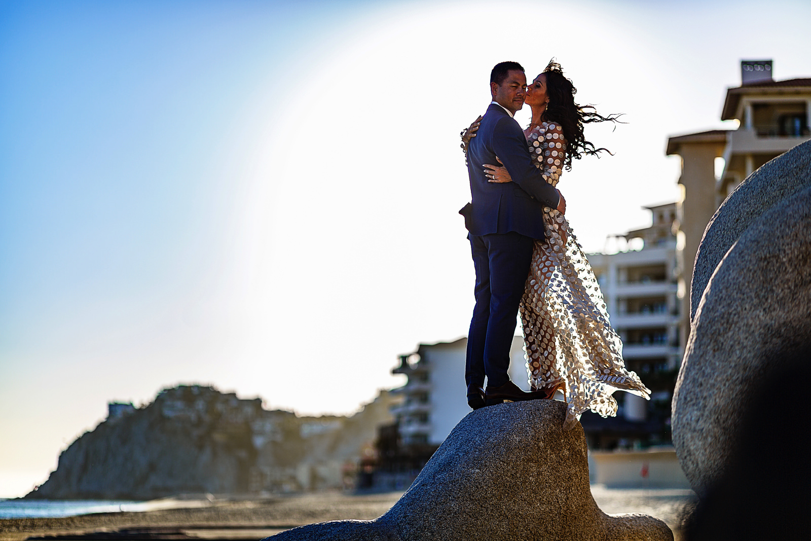 Bride and groom on top of a rock against the wind in Cabo San Lucas