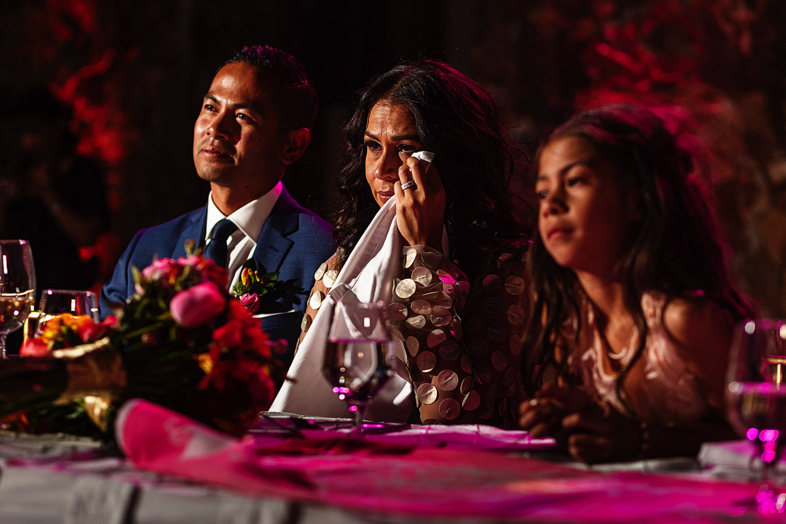 Bride crying next to her husband and daughter during a speech