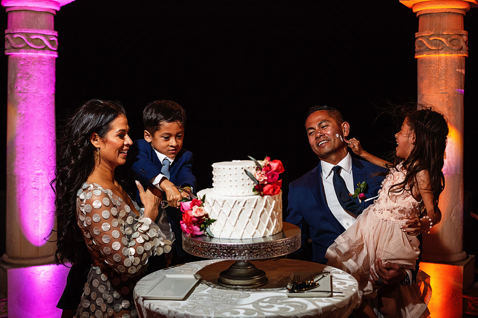 Groom, bride and kids having fun at the cake cutting part of their wedding