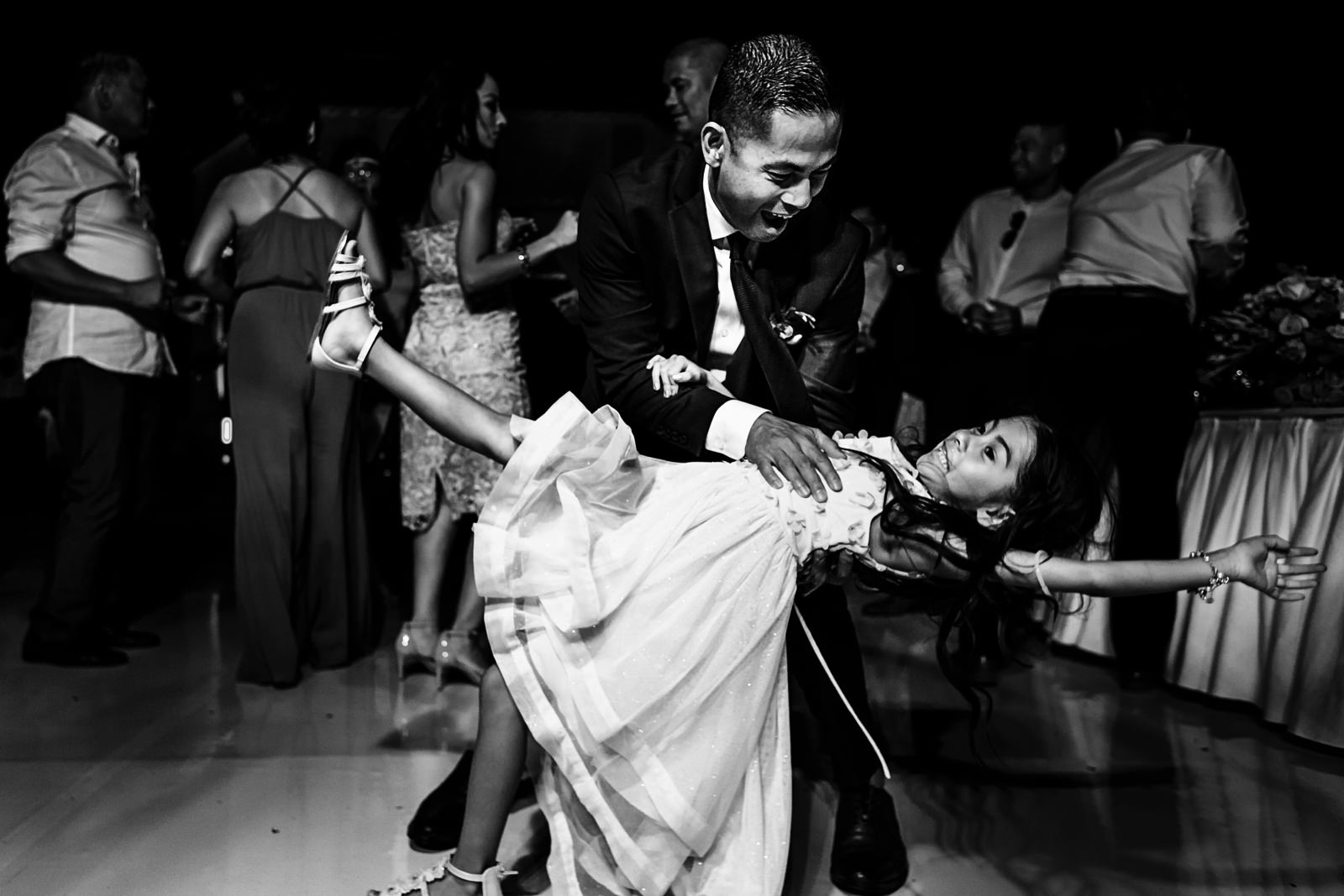 Groom dancing and leaning his daughter at the dance floor