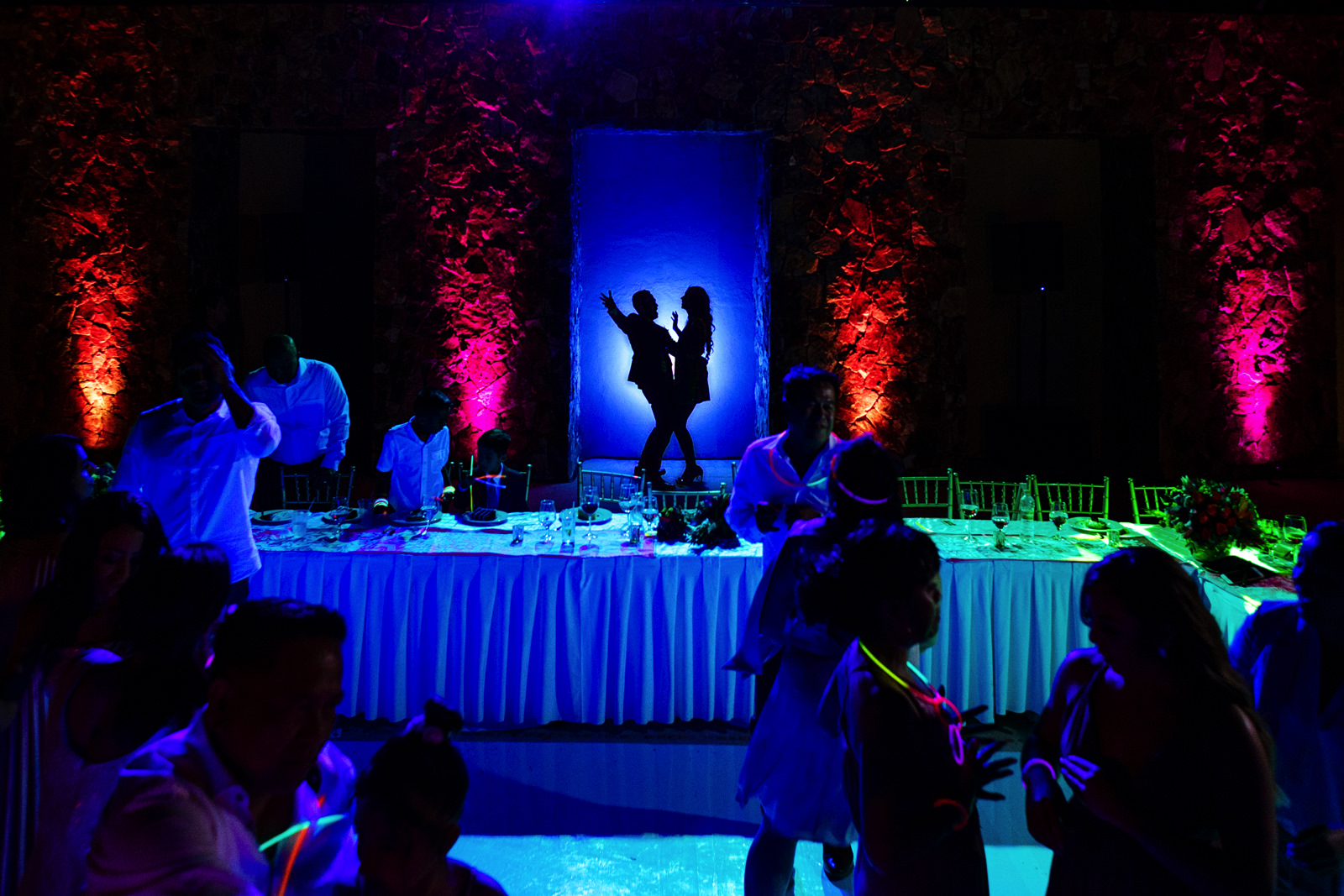Bride and groom silhouette of them dancing while their guests