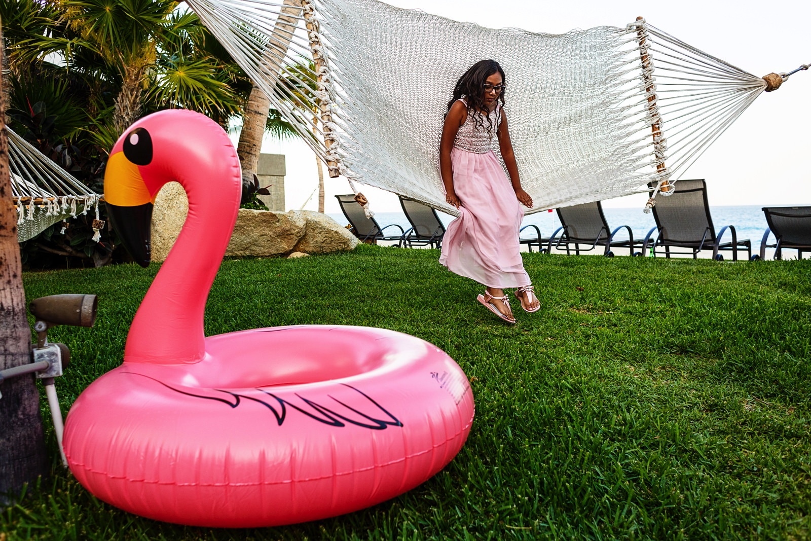 Girl swinging on a hammock on the grass area next to a pink flamingo floatier