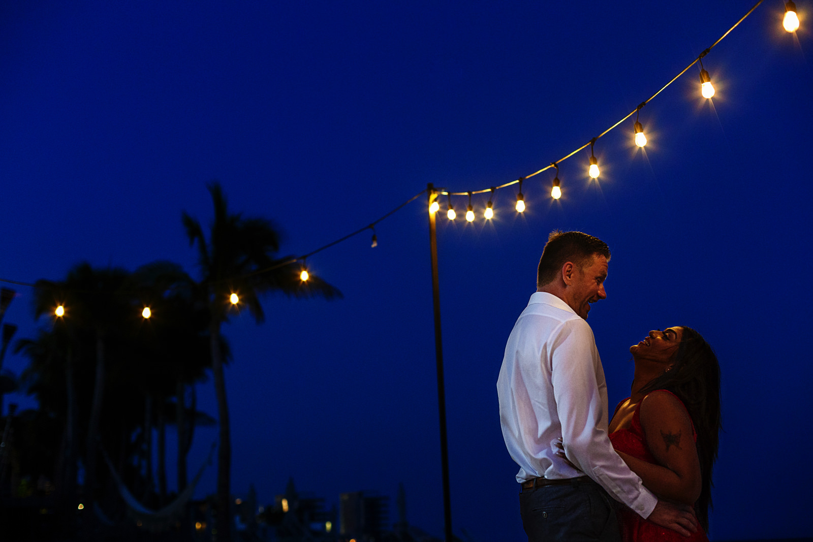 Couple facing at each other under light bulbs against the blue sky at night