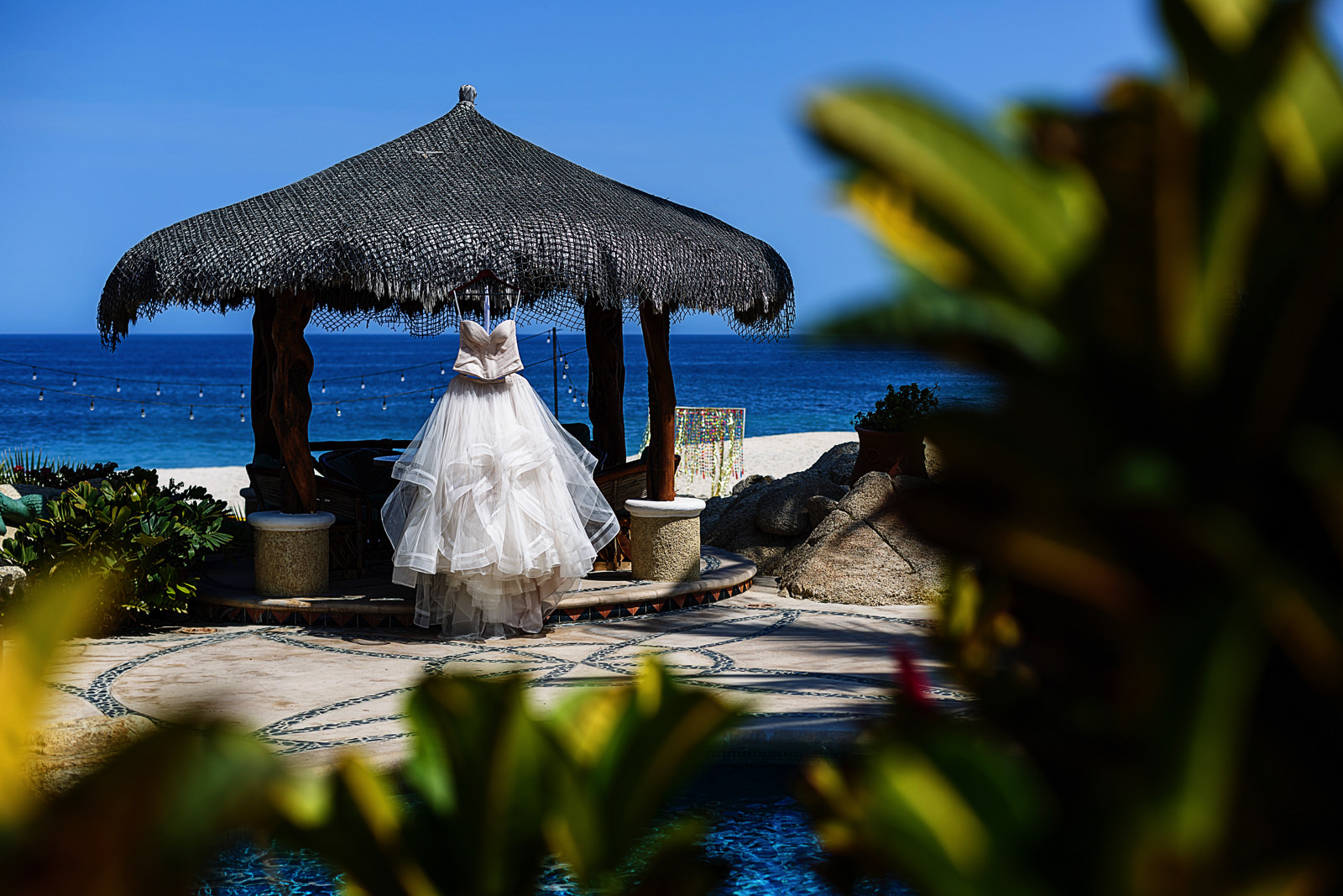 Wedding dress hanging from a palapa