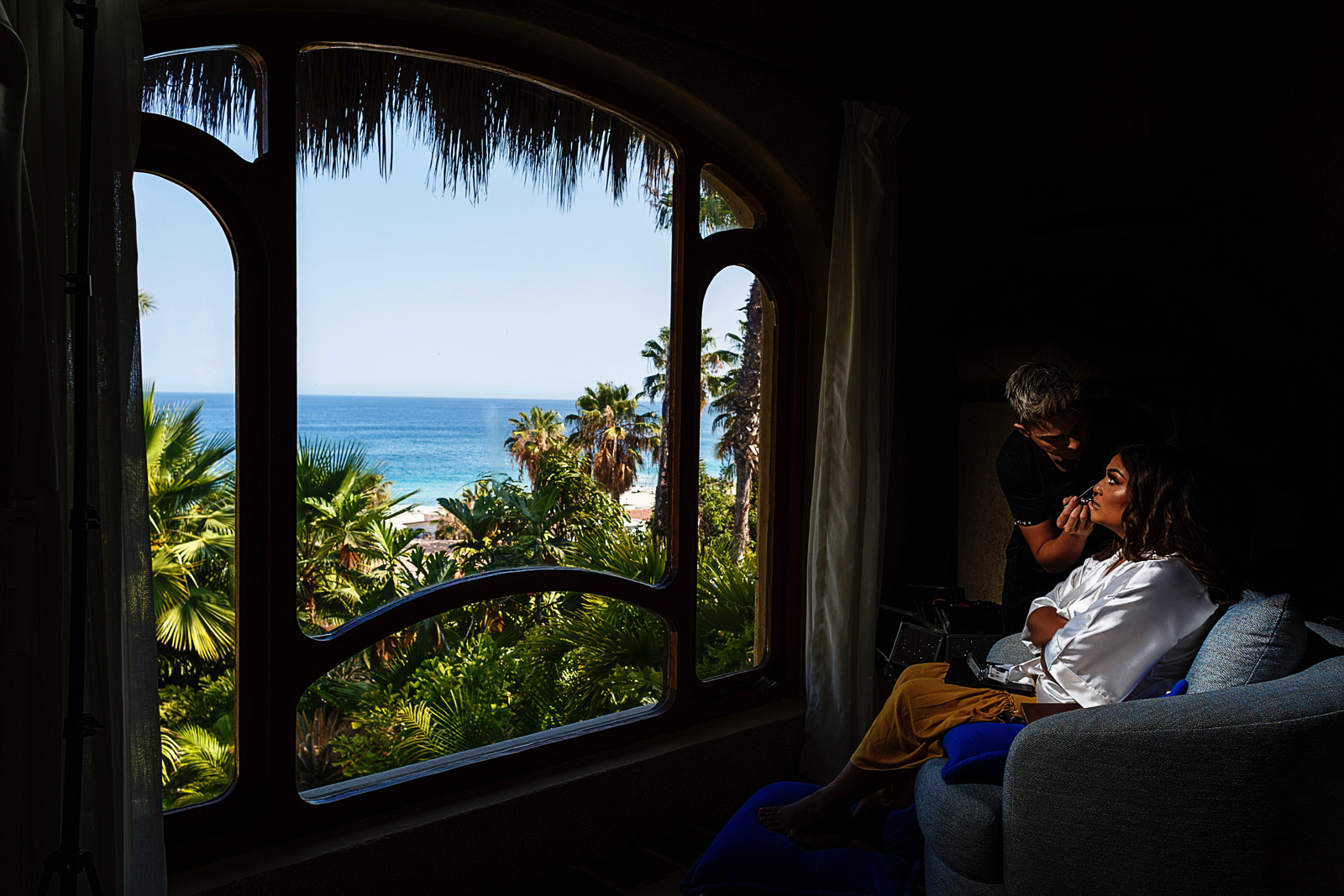 Bride during her make-up is getting applied in front of a window with a great view of the ocean at Villa Las Rocas in Cabo San Lucas