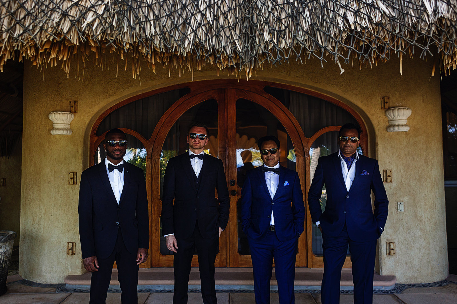 Groom and groomsmen standing outside the main room's door at Villa Las Rocas in Cabo San Lucas, Mexico.