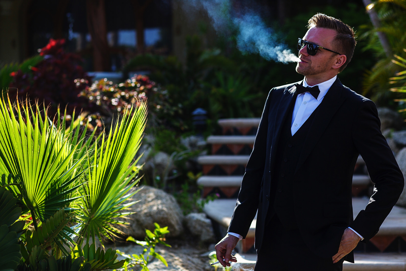 Groom smoking a cigarette wearing a tuxedo