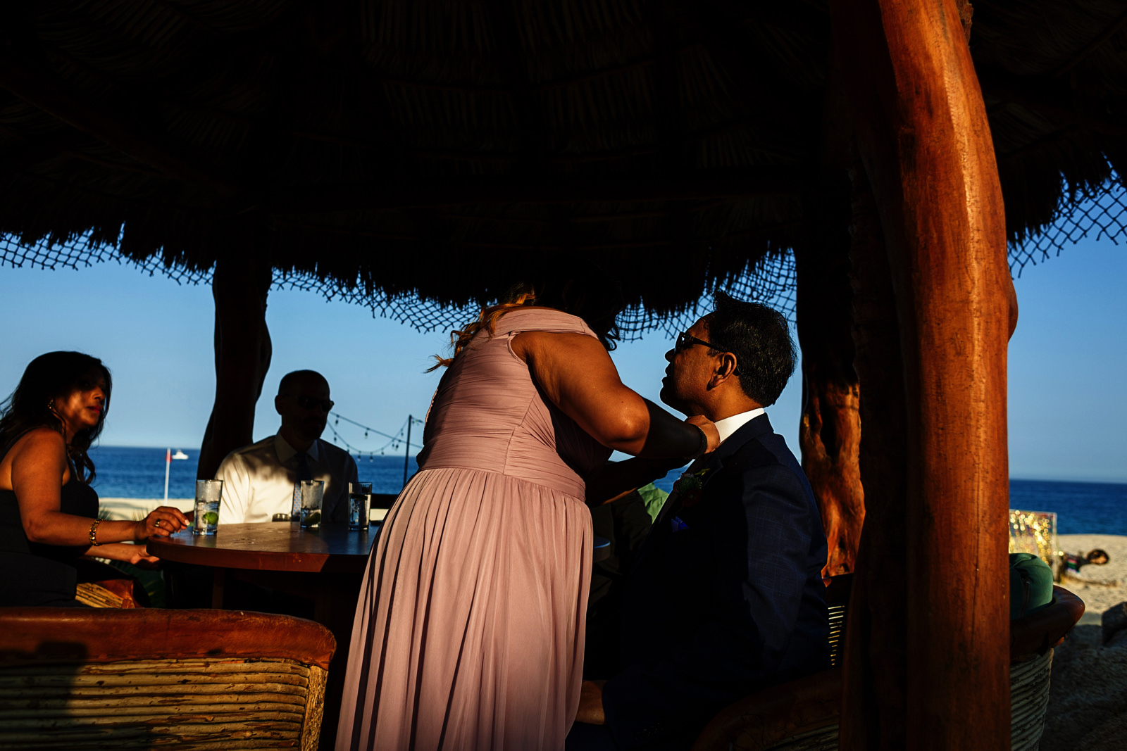 A guest is getting his bow tie adjusted by another guest under a palapa