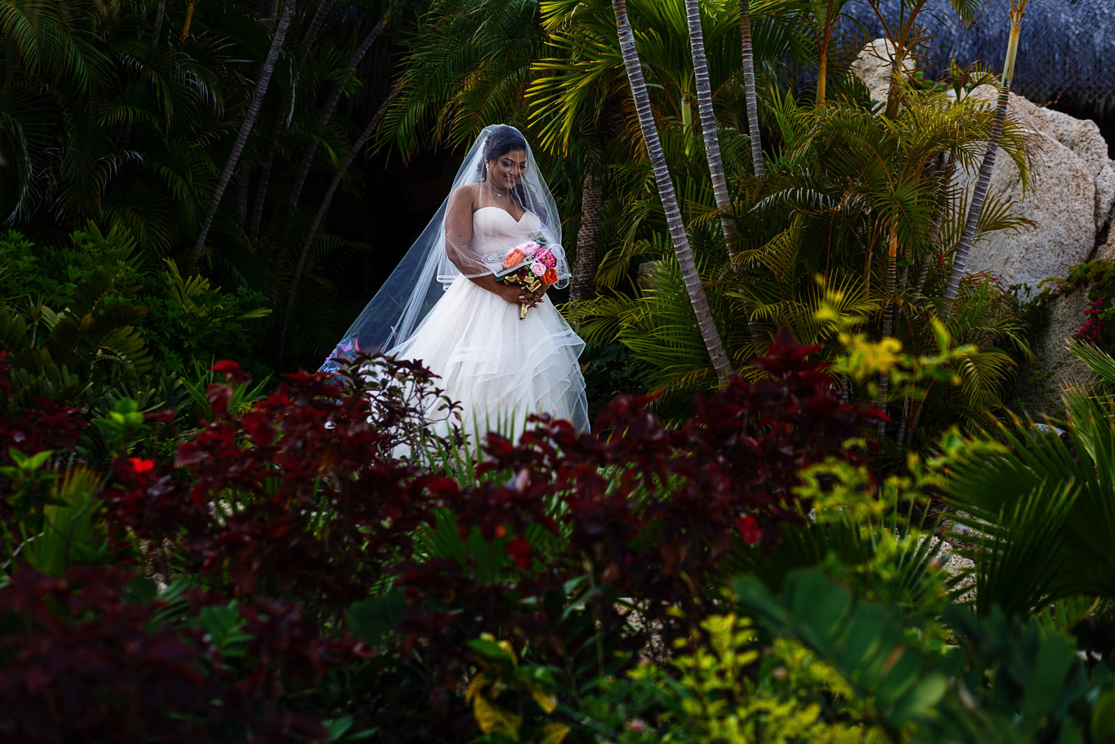 Bride surrounded by greenery with different plants and colors