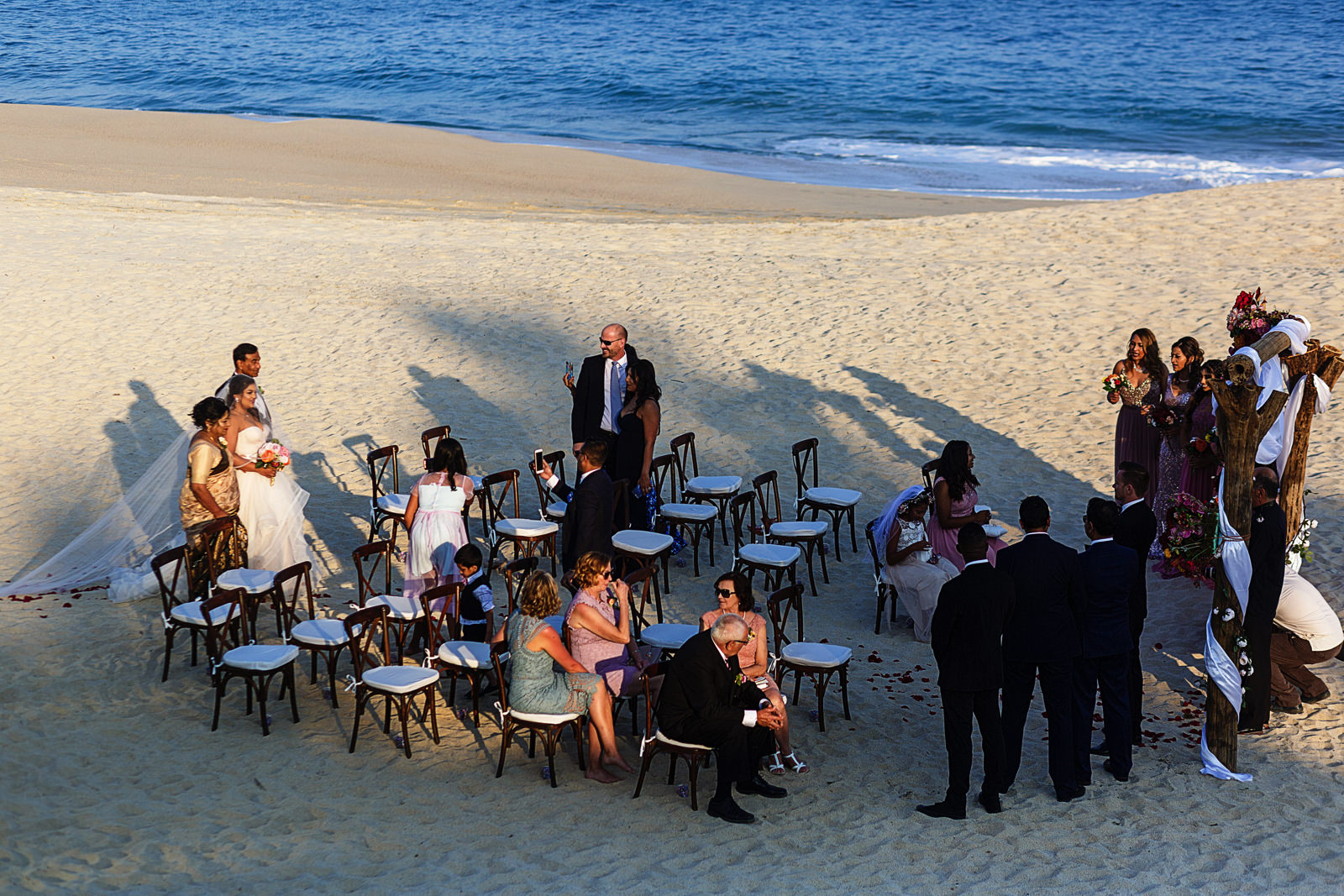 Bride with parents down the aisle at the wedding ceremony on the beach in Cabo San Lucas