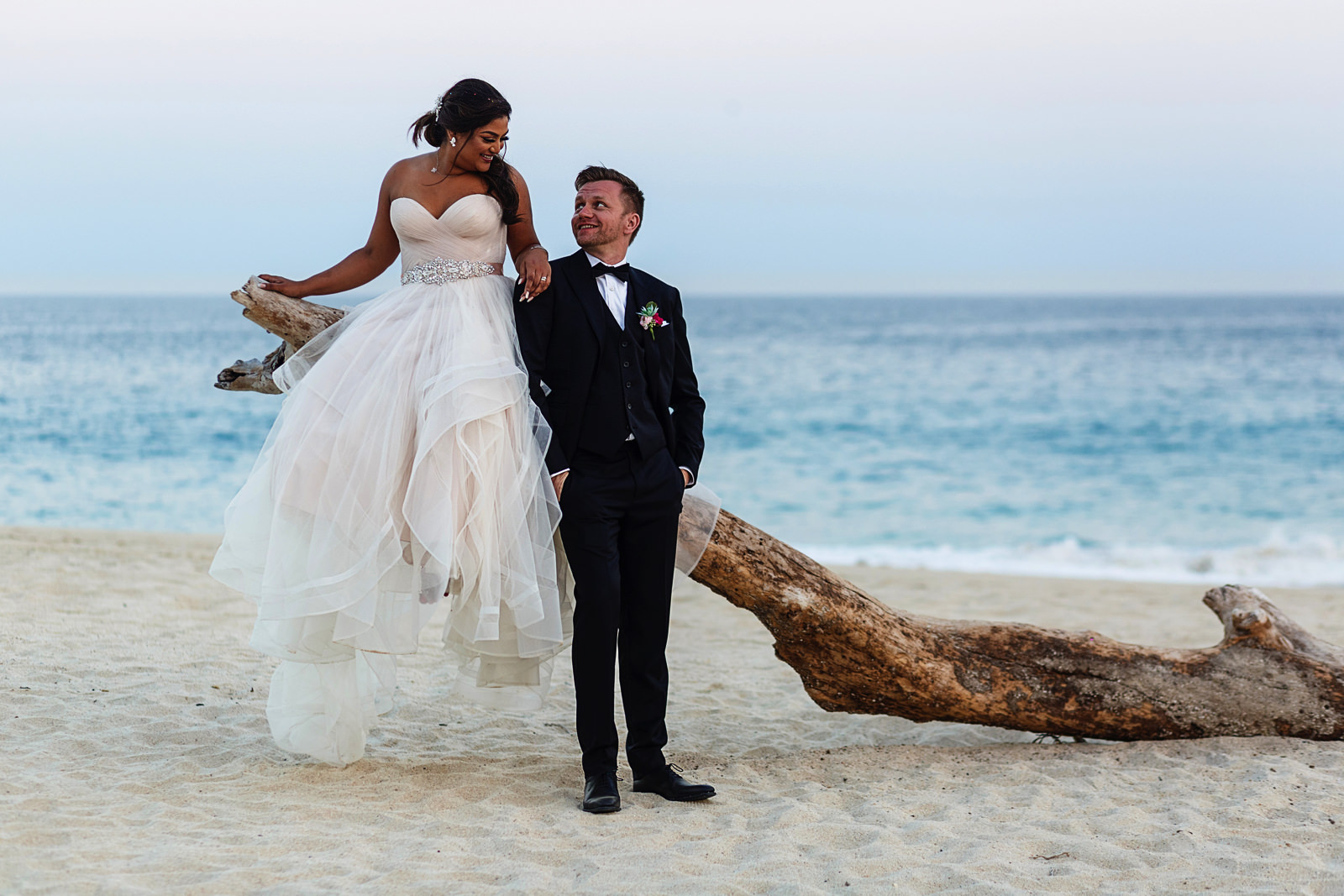 Bride sitting on a log in the beach and groom leaning against it in Cabo San Lucas, Mexico.