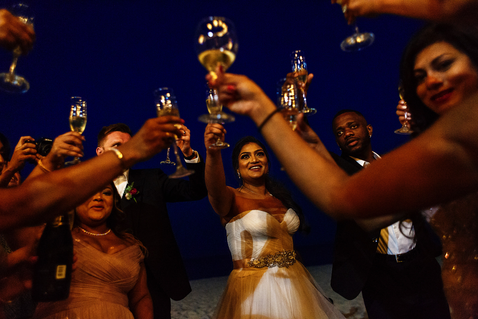 Bride toasts with champagne to friends and family at dawn