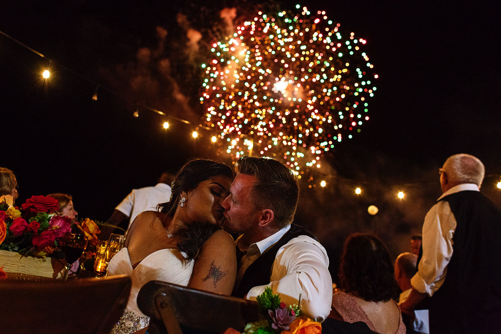 Bride and groom kiss sitting at the table while fireworks light the sky