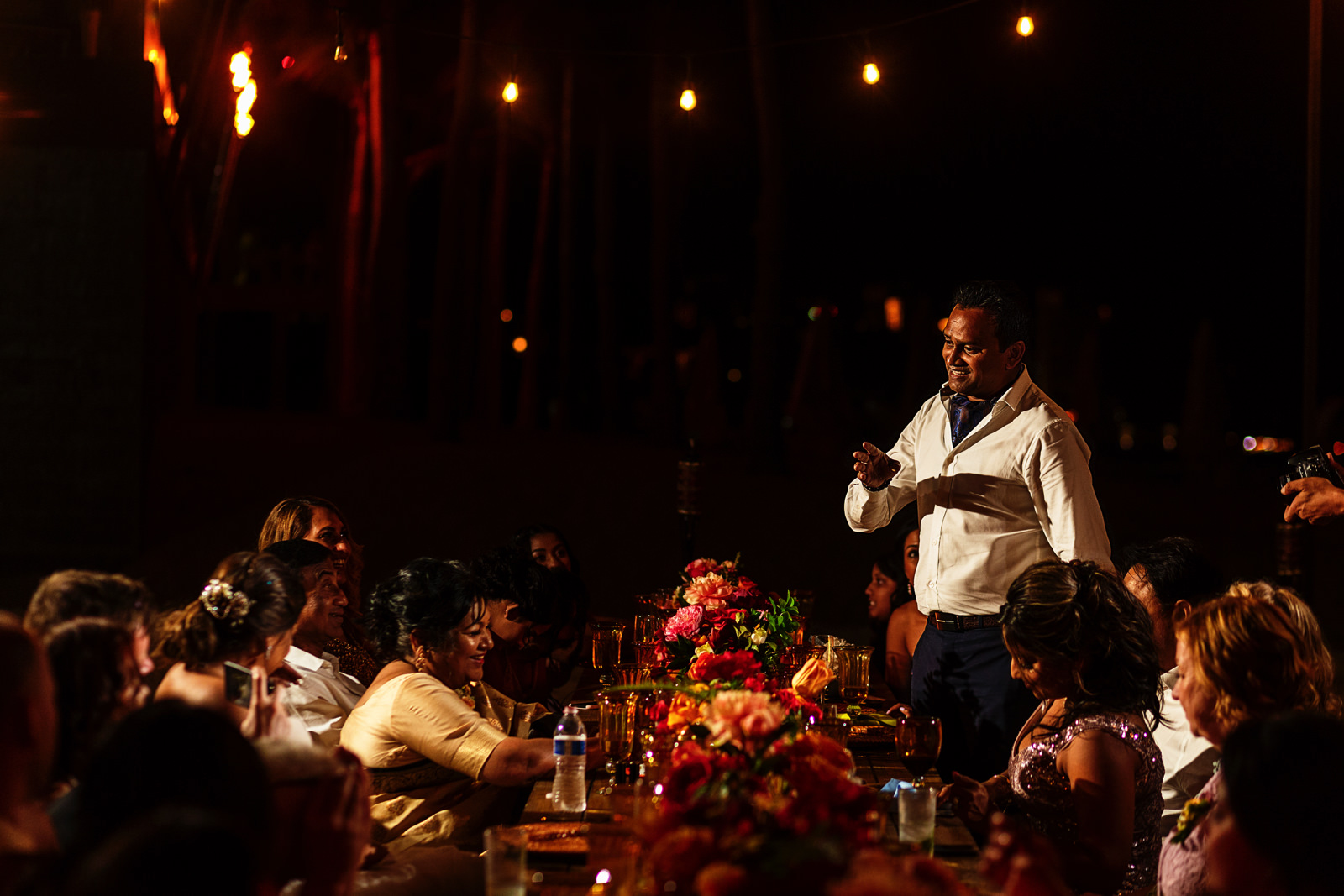 A wedding guest is giving a speech standing during dinner at the table