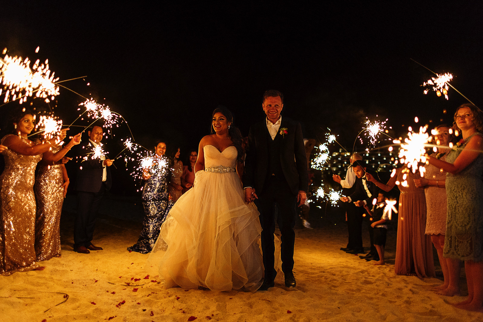 Groom and bride surrounded by their friends and family that hold sparklers at night