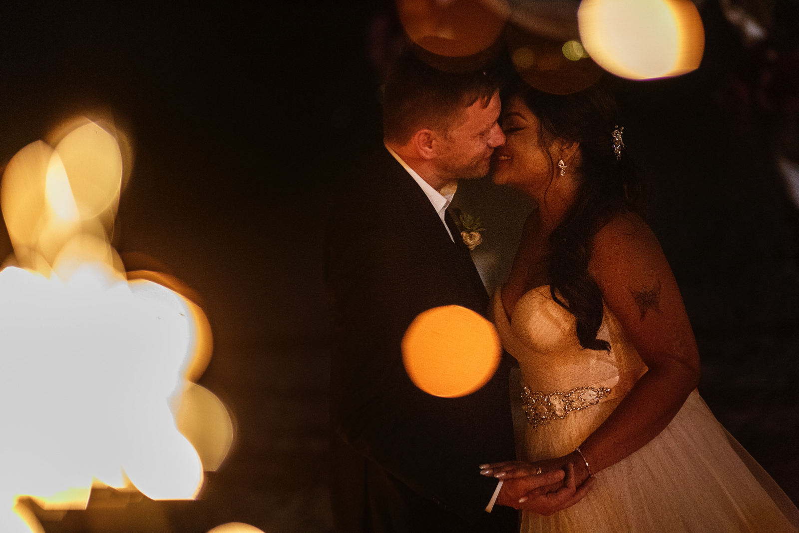 Groom and bride kiss through the sparkler's embers