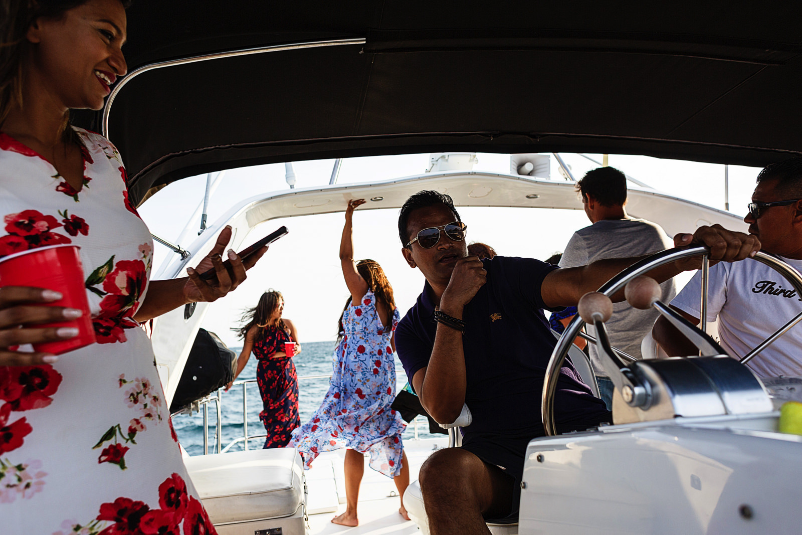 A man steering the yacht while the rest party and dance