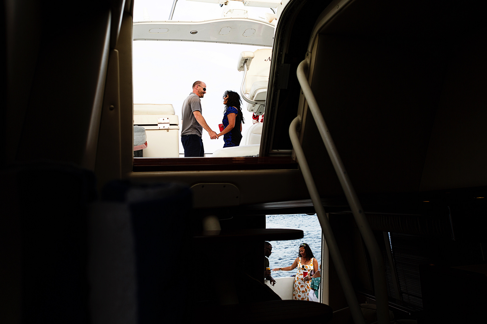 Couple dance on the upper deck and another couple chat in the lower deck of the yacht