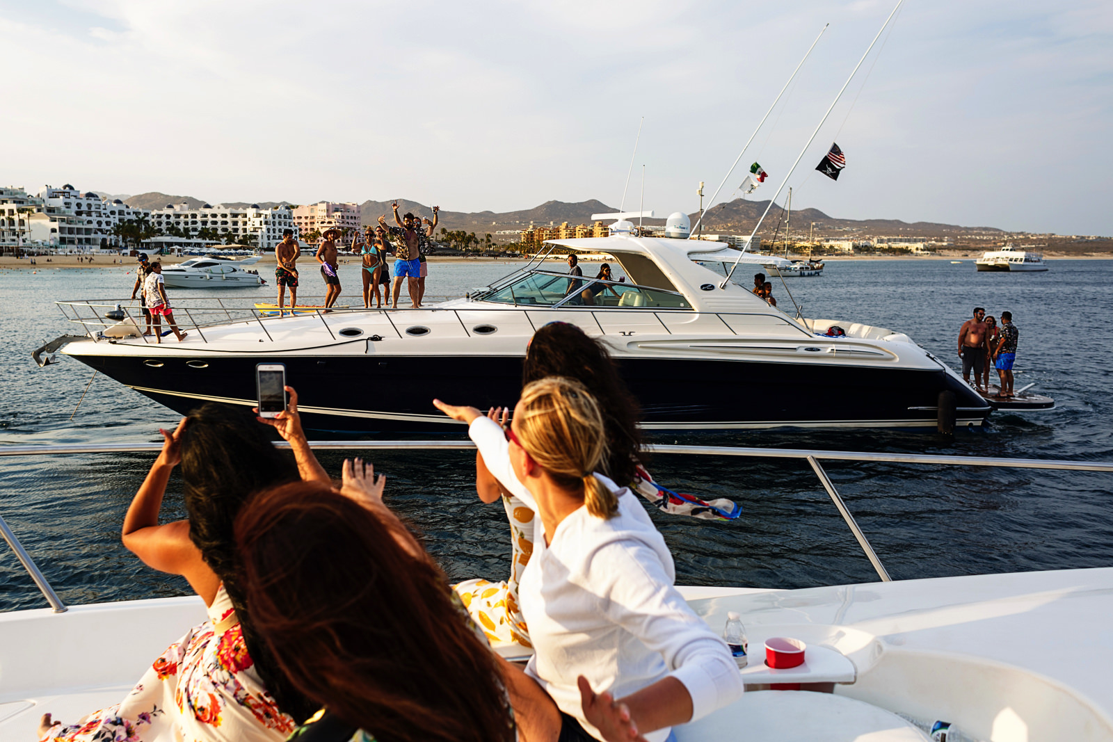 Waving hello to another yacht that is also partying at Cabo San Lucas