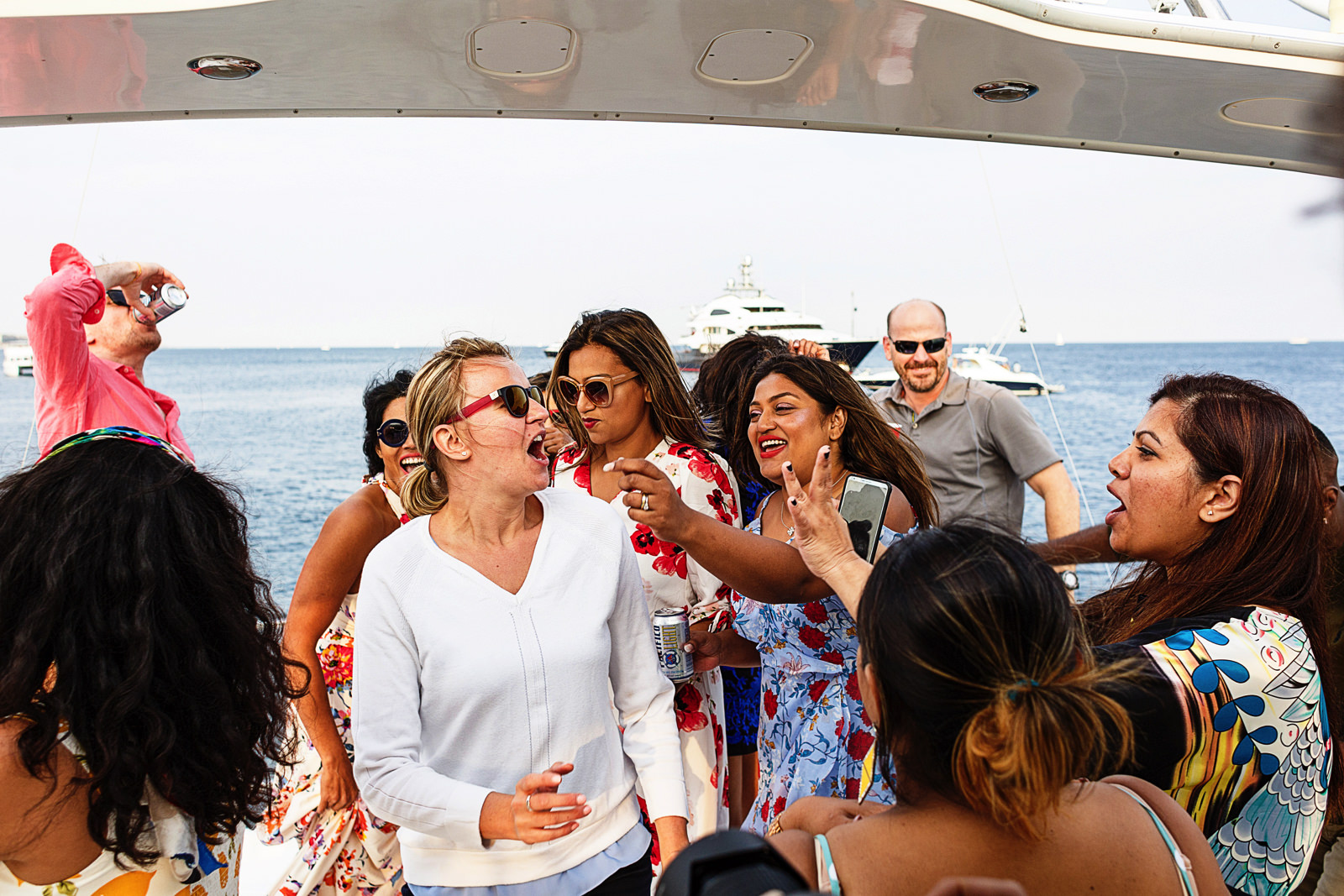 Group of people dancing and partying on the upper deck of a yacht