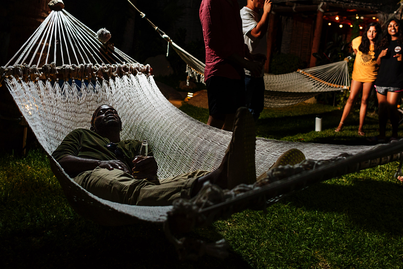 A man is falling sleep on a hammock at the party on the grass area