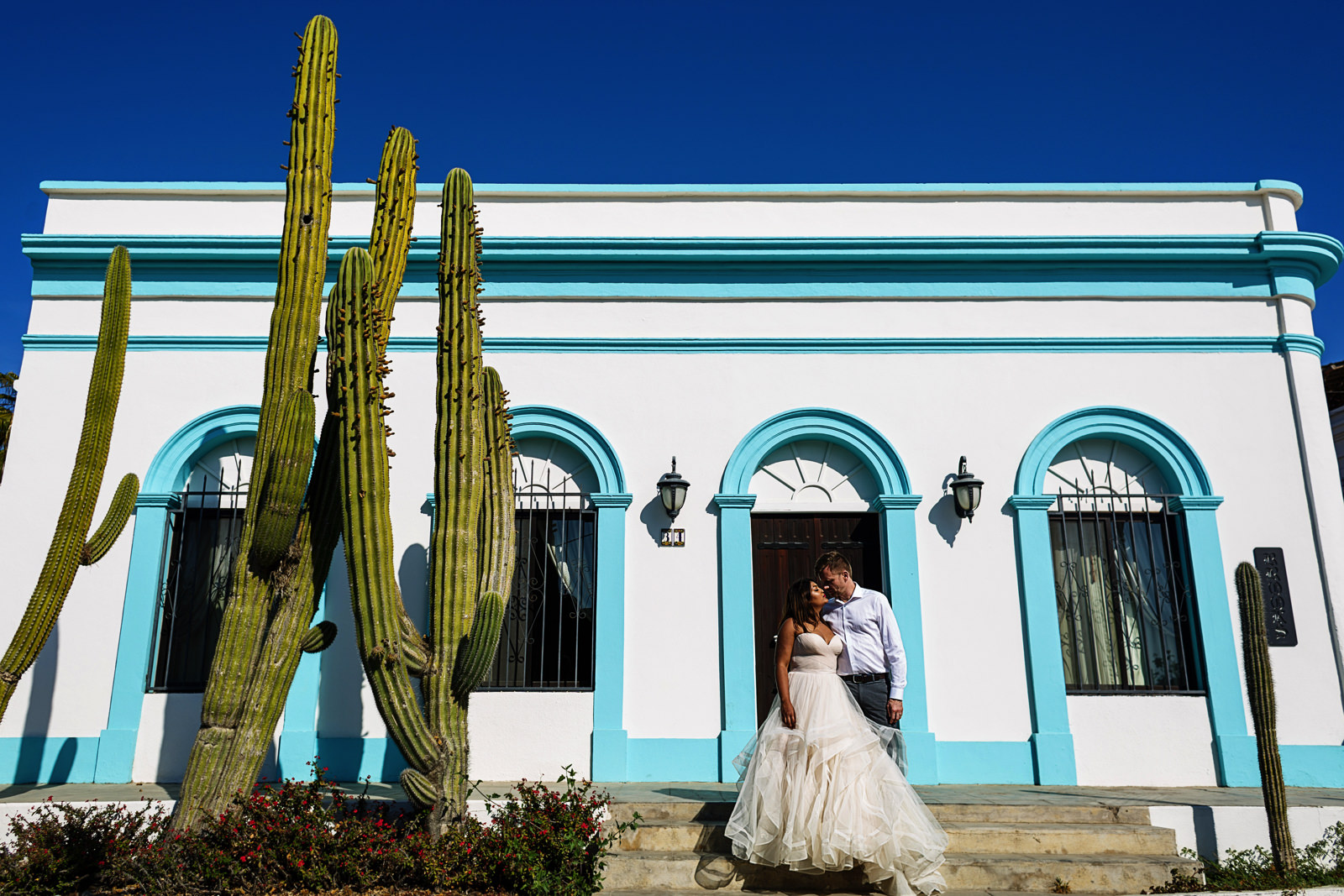 Bride and groom standing outside a Todos Santos house with a peculiar facade with a cactus