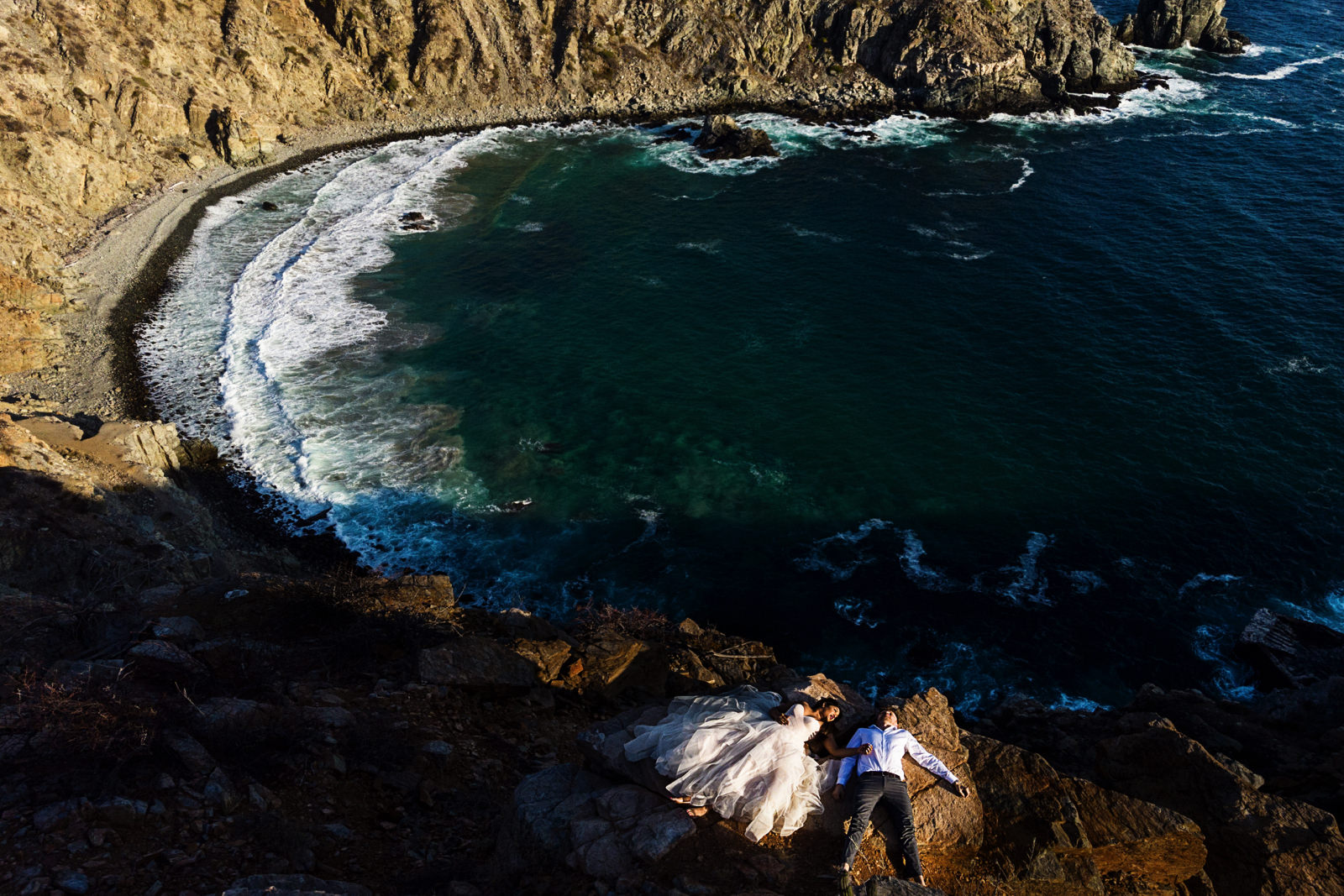 Bride and groom laying on top of a cliff in Punta Lobos close to Todos Santos, Mexico