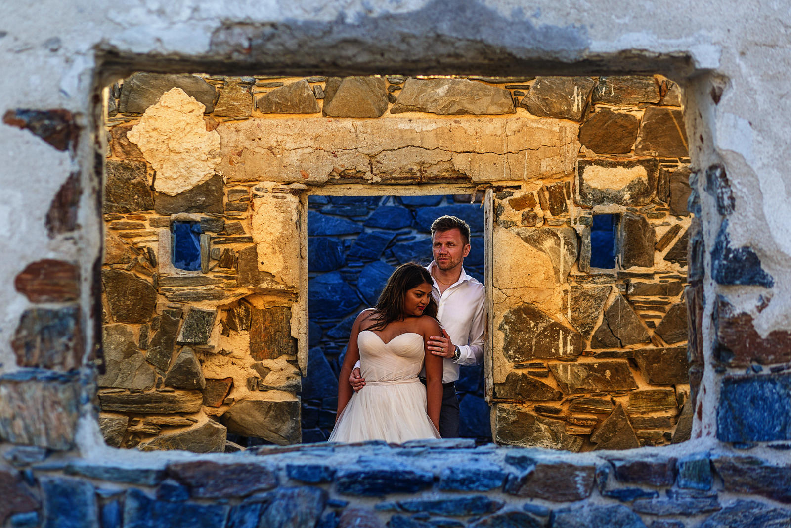 Bride and groom leaning on a doorway frame at the semi-ruins nearby Hotel San Cristobal in Todos Santos, Mexico
