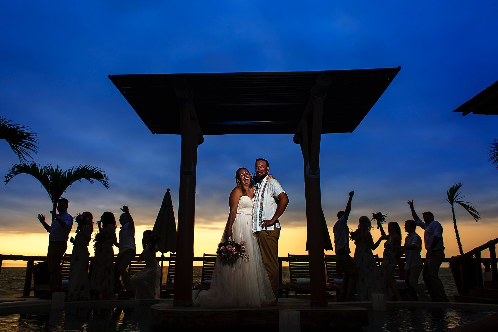 groom-bride-bridal-party-sunset-happy-wild-crazy-magmod.jpg