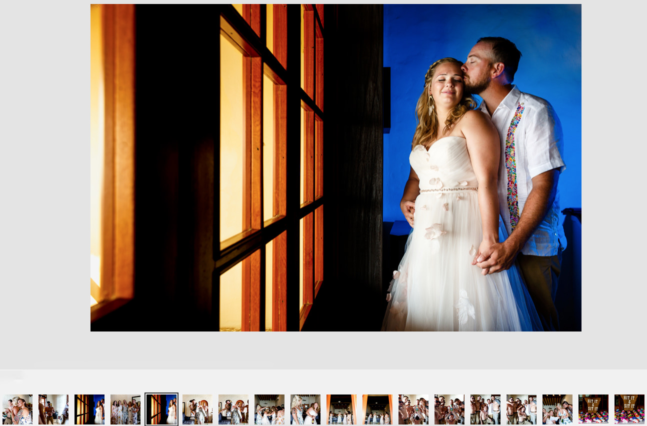 Bride and groom standing in front of a window against a blue illuminated wall