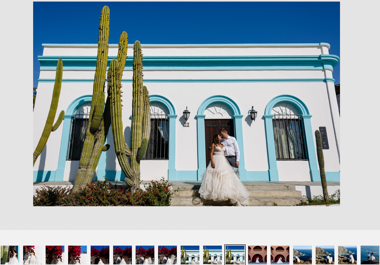 Married couple of groom and bride standing outside a famous and painteresque house in Todos Santos, Baja California, Mexico.