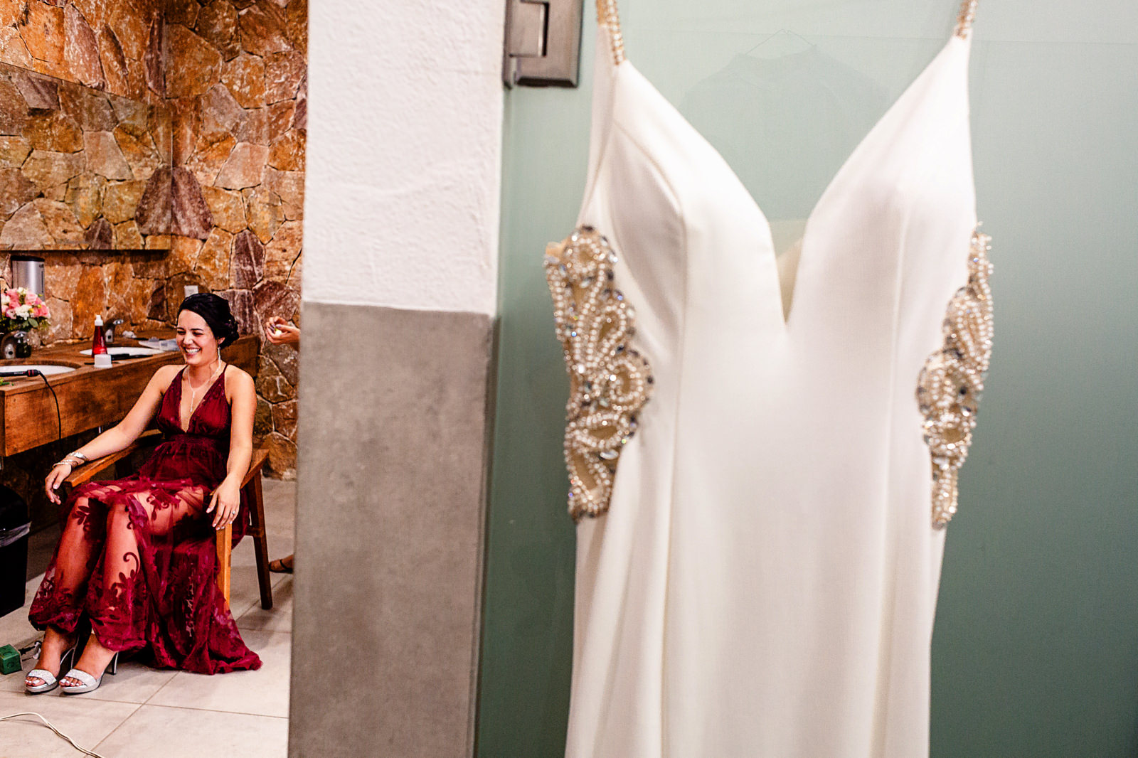 Bride laughing while getting ready at the bathroom in La Patrona beach club, her wedding dress is hanging before her.