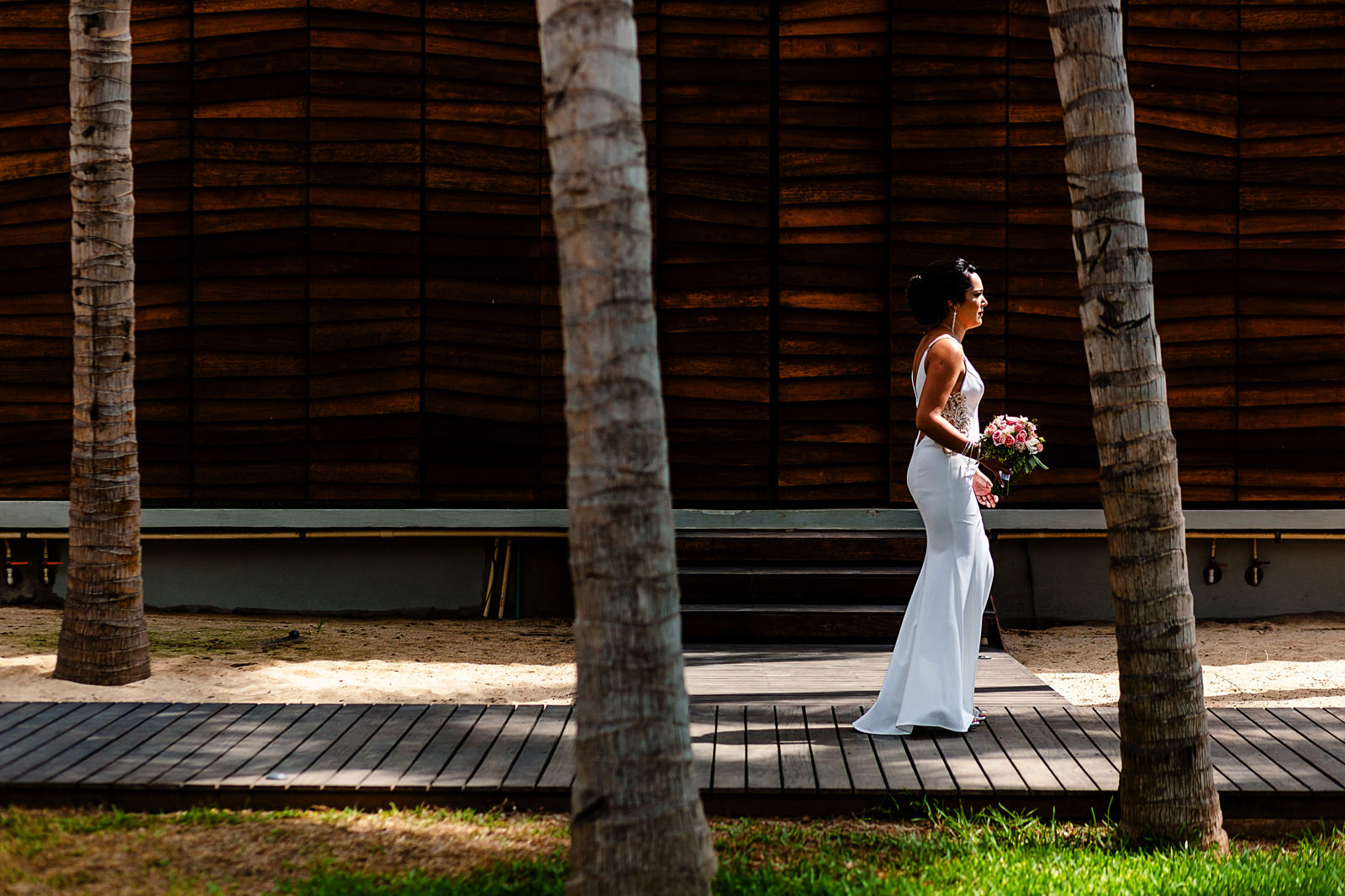 Bride walking in front of a woodwork wall between three palm trees.