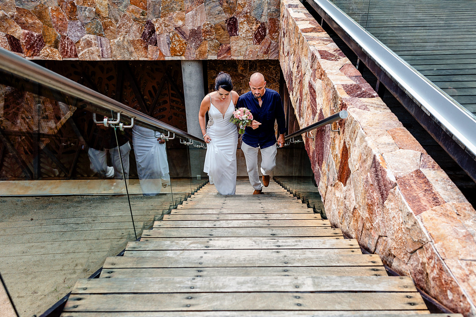 Bride and her dad walking up the stairs to the wedding ceremony.