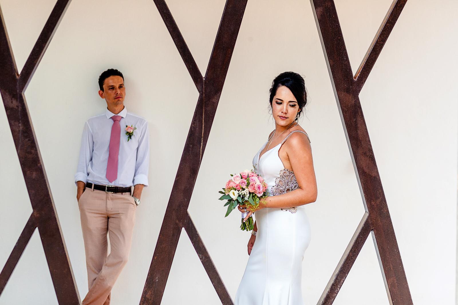 Bride and groom standing between geometrical metal structures.