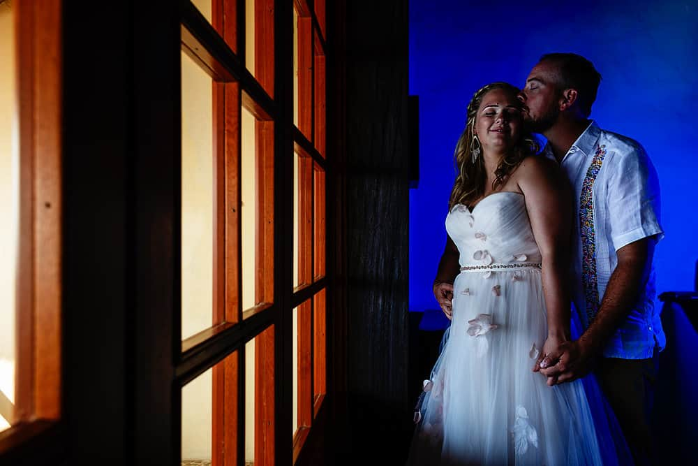 Bride and groom standing in front of a window with a blue light wall behind them.