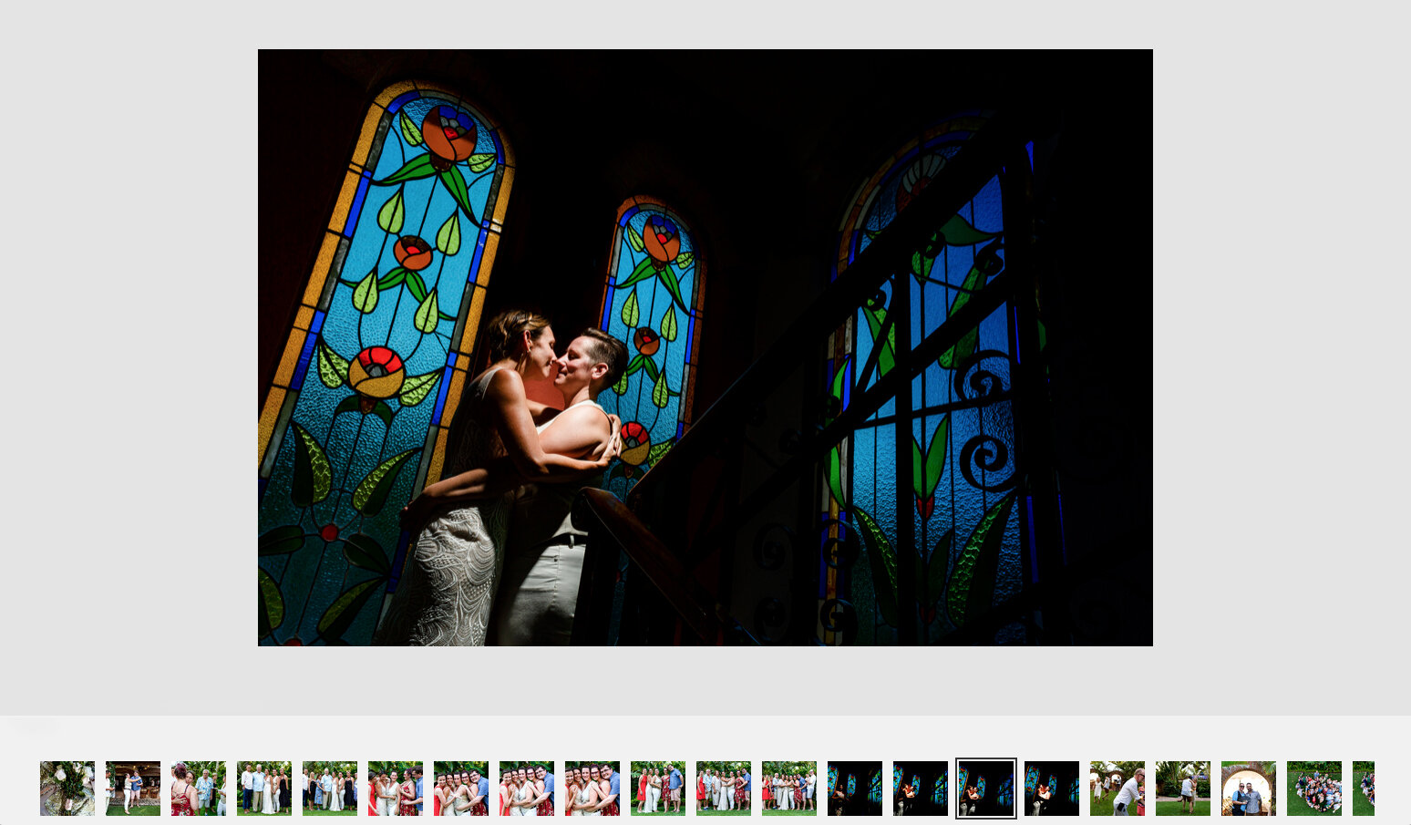 Lesbian couple on their wedding day posing in the staircase next to stained glass.