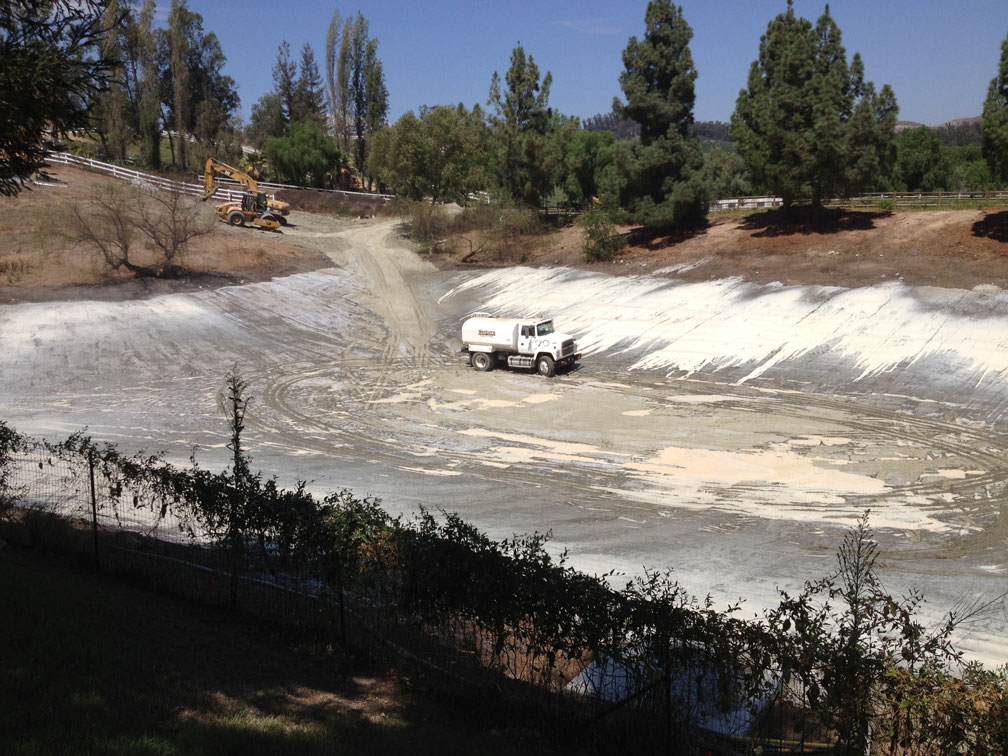 To waterproof the pond, a thin layer of local clay was imported, mixed with a vegetable-based sealant, compacted, and sprayed again. This image shows a water truck spreading the final sealant coat.