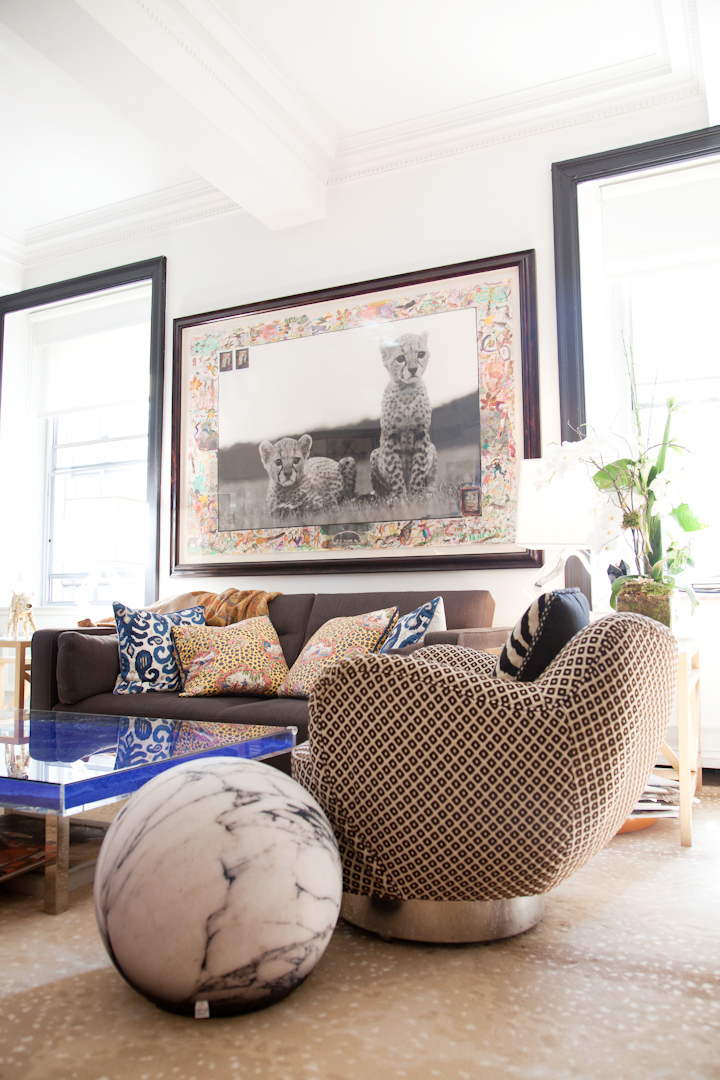 "Chic and tasteful: carpet by Beauvais, vintage-modern armchairs, Yves Klein Coffee table and round ""marble-like"" ottoman from Barney's"