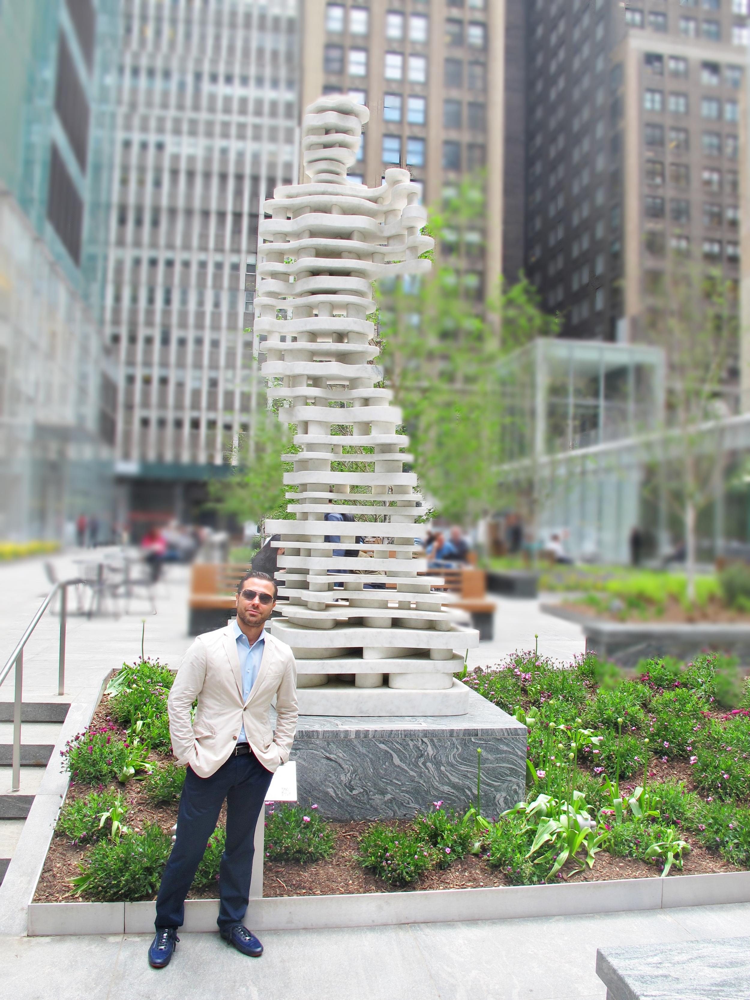 """Antonio standing in front of his sculpture """"Hero"""""""