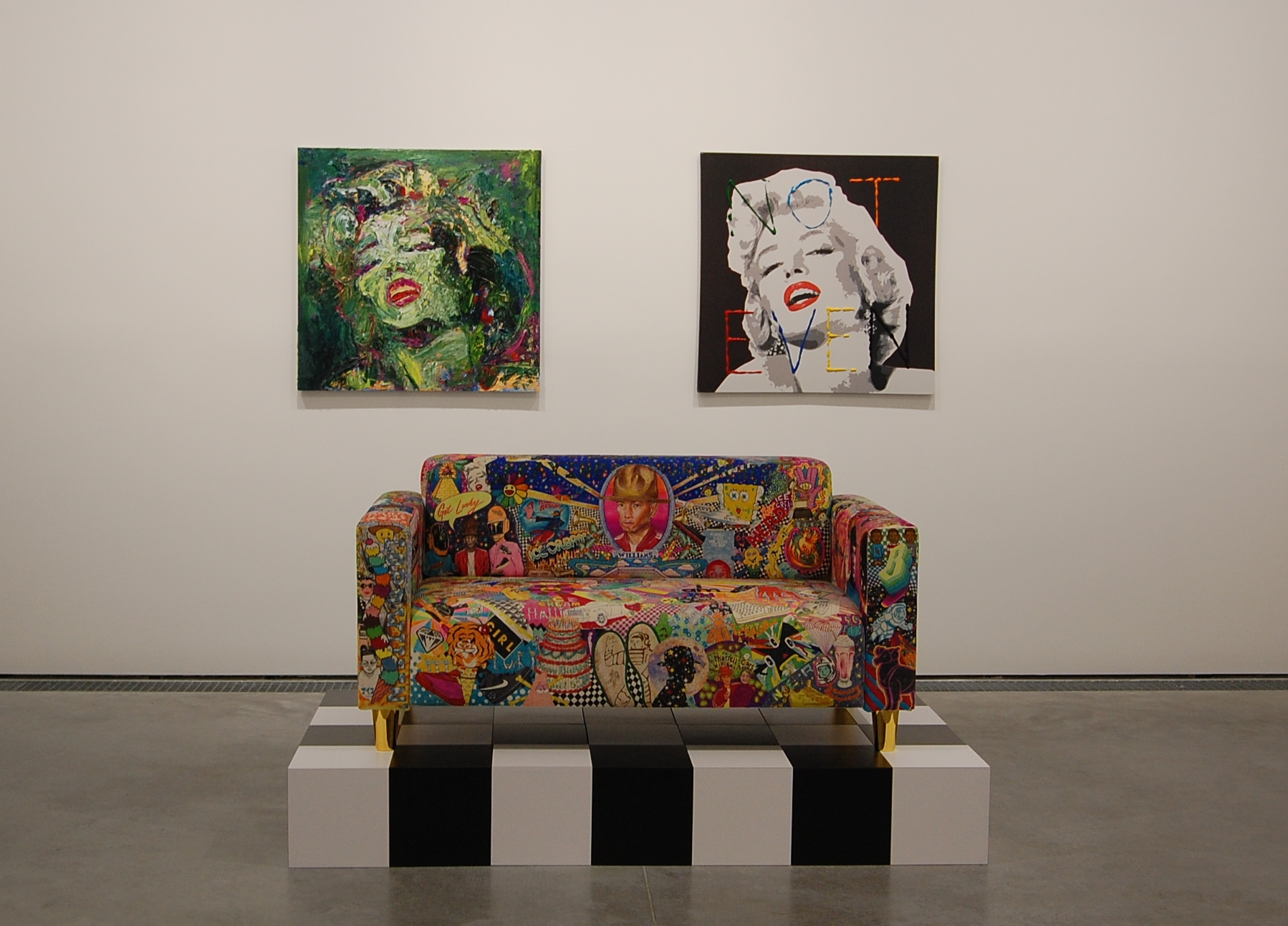The paintings and the loveseat are by Rob Pruitt