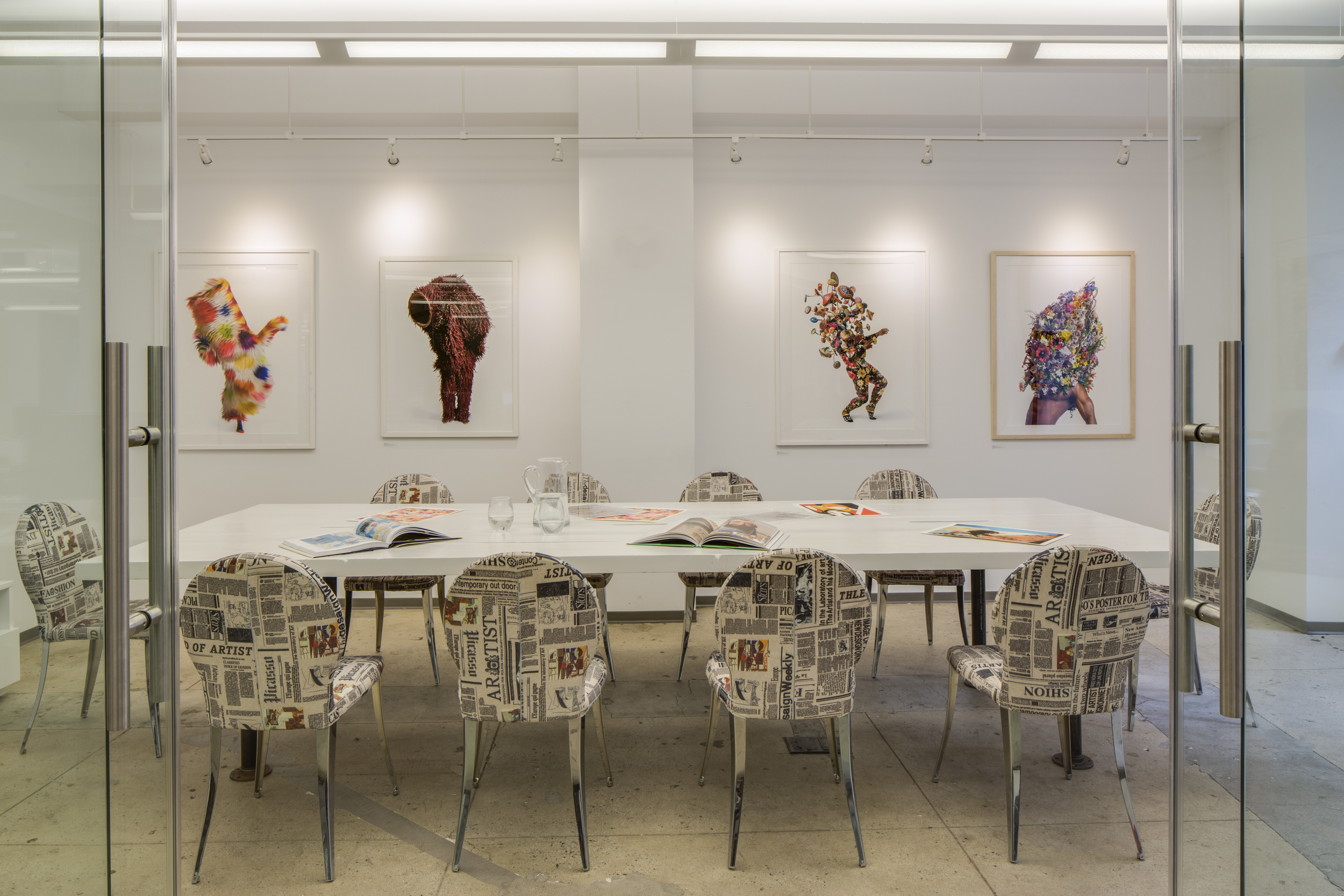 The conference room with Eurostyle chairs upholstered in newspaper fabric. The photographs on the wall are a limited edition by Nick Cave for Artspace.