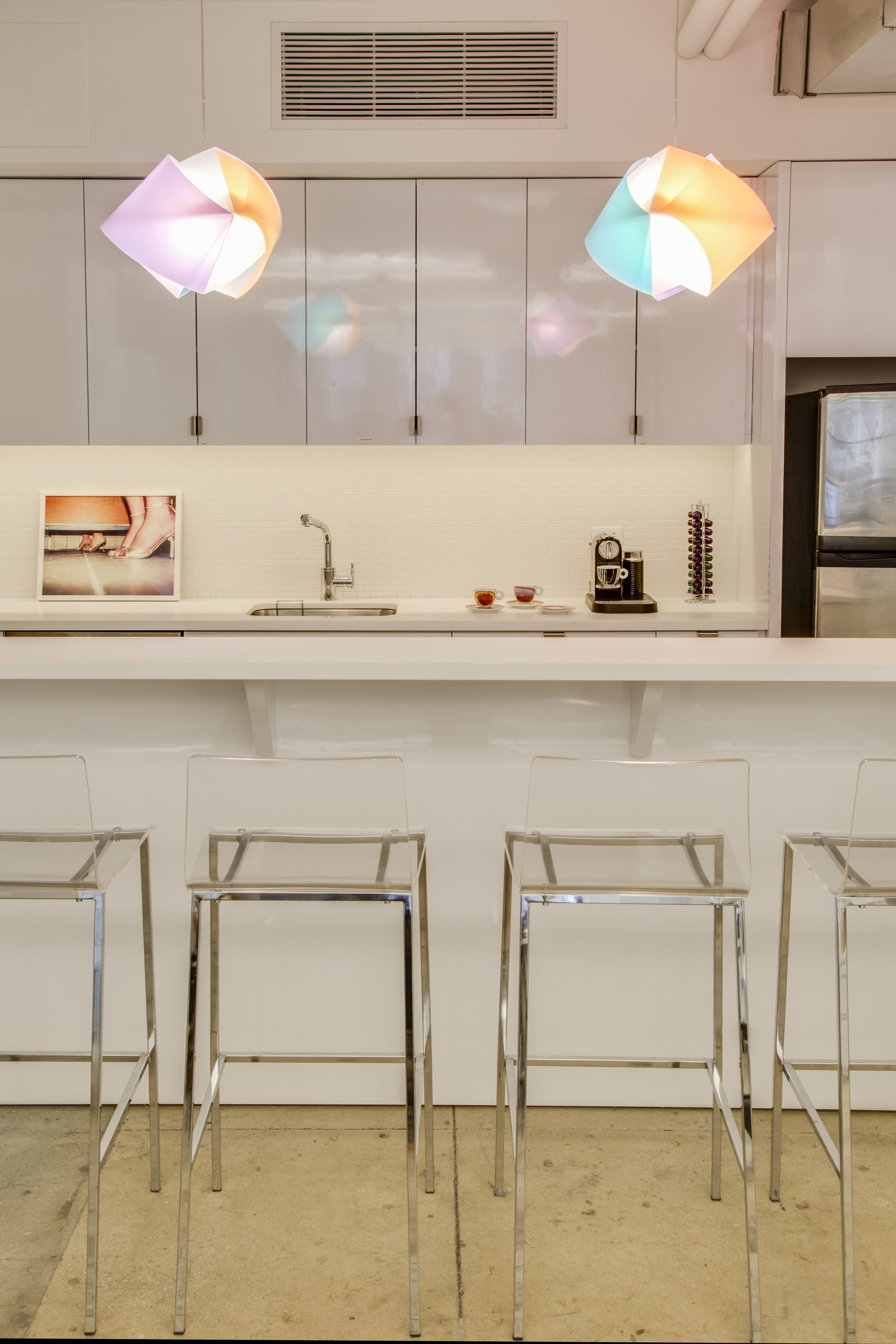 The kitchen area with SLAMP pendants and lucite barstools. The photograph on the back is by Christopher Anderson.