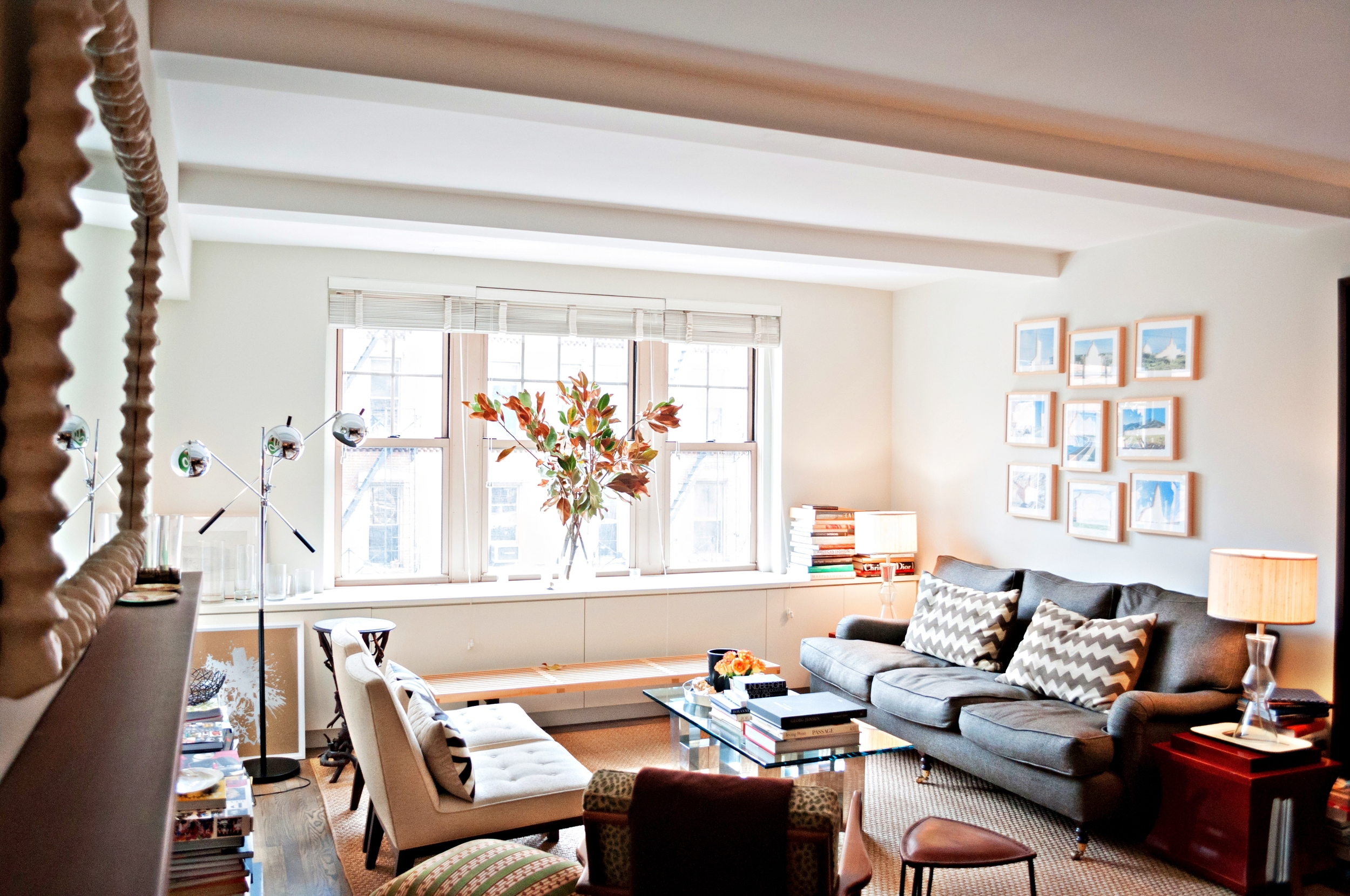 """Peter's living room is sunny and bright. The Jose Davila arrangement of""""Buildings You Have to See Before You Die"""" on top of the sofa is a subtleeye-catcher. I remember seeing this particular series for the first time at Art Basel Miami Beach in 2008."""