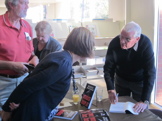 Reece signing 'Murder on Display' for a buyer, at the Tea Tree Gully Library book launch.