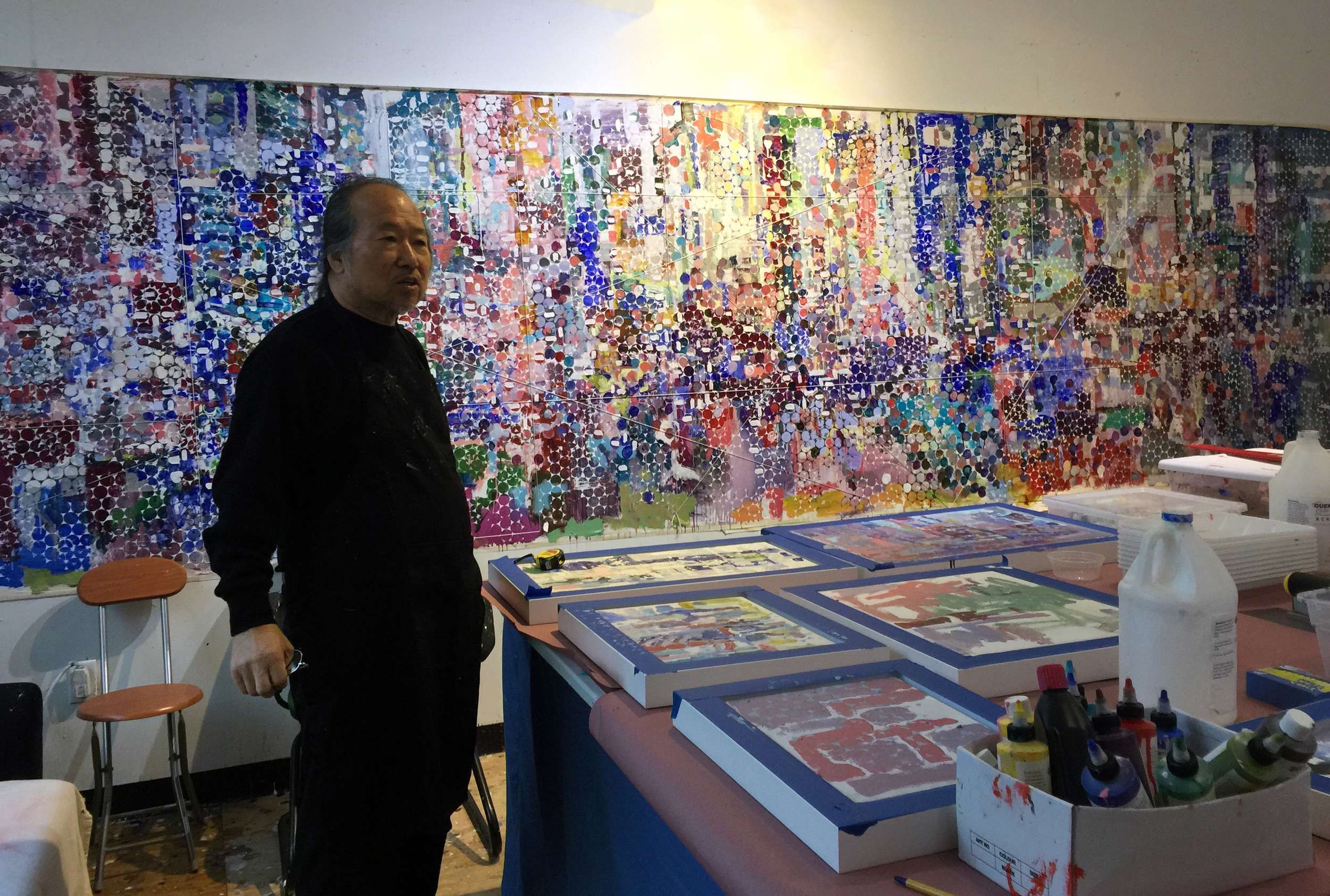 The artist standing in front of a work in progress