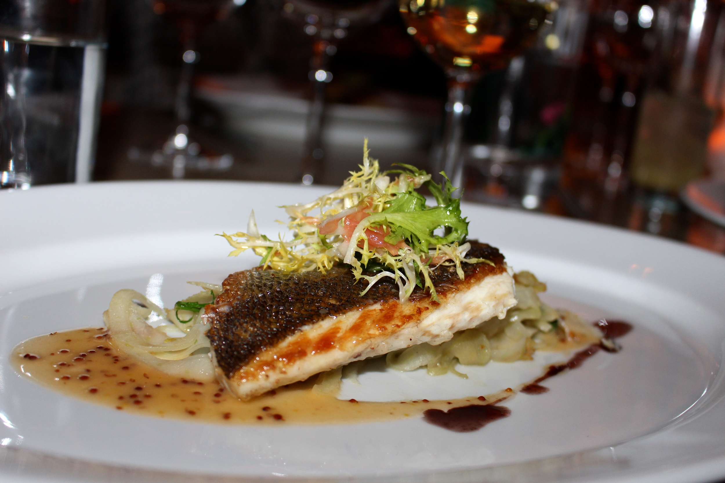 Rosated branzino with lightly roasted fennel fricasee, grapefruit pommery emulsion.