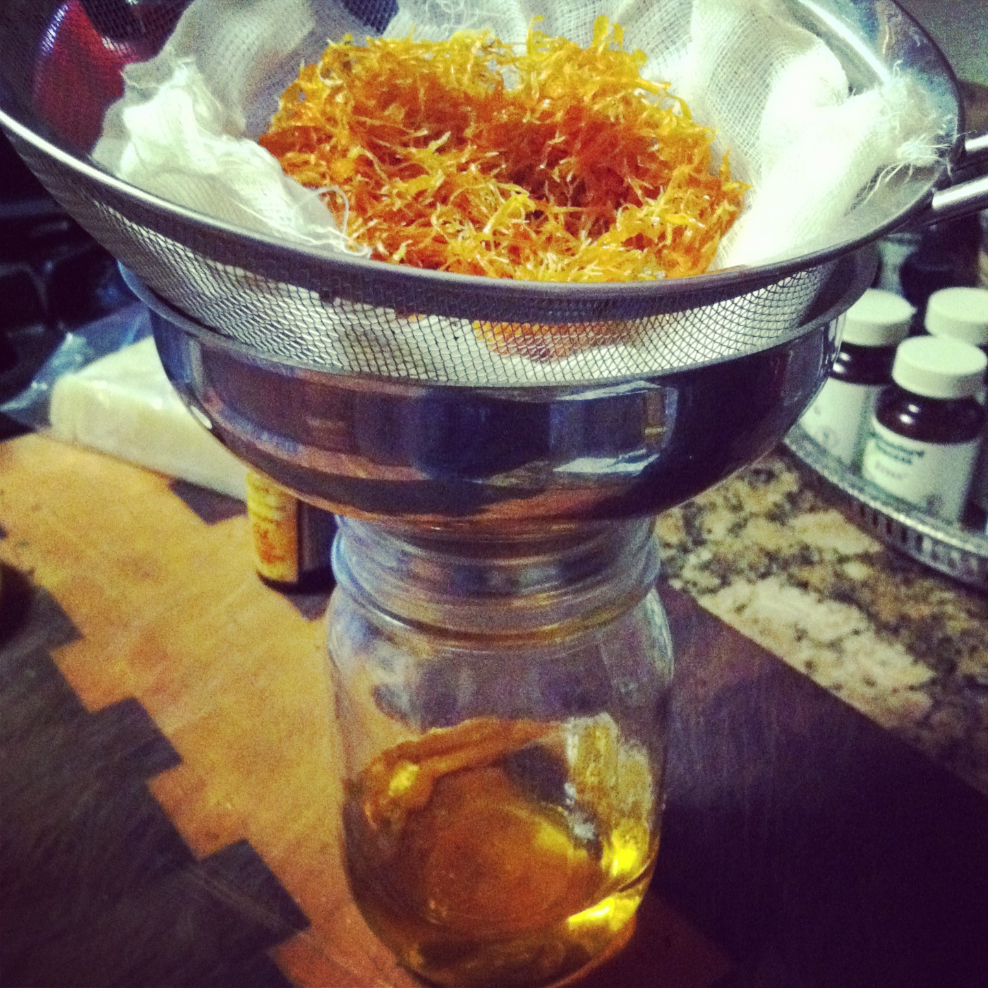 Straining homegrown calendula leaves out of an oil infusion. We grow the lavender I infuse into  alchemy*oil  as well.