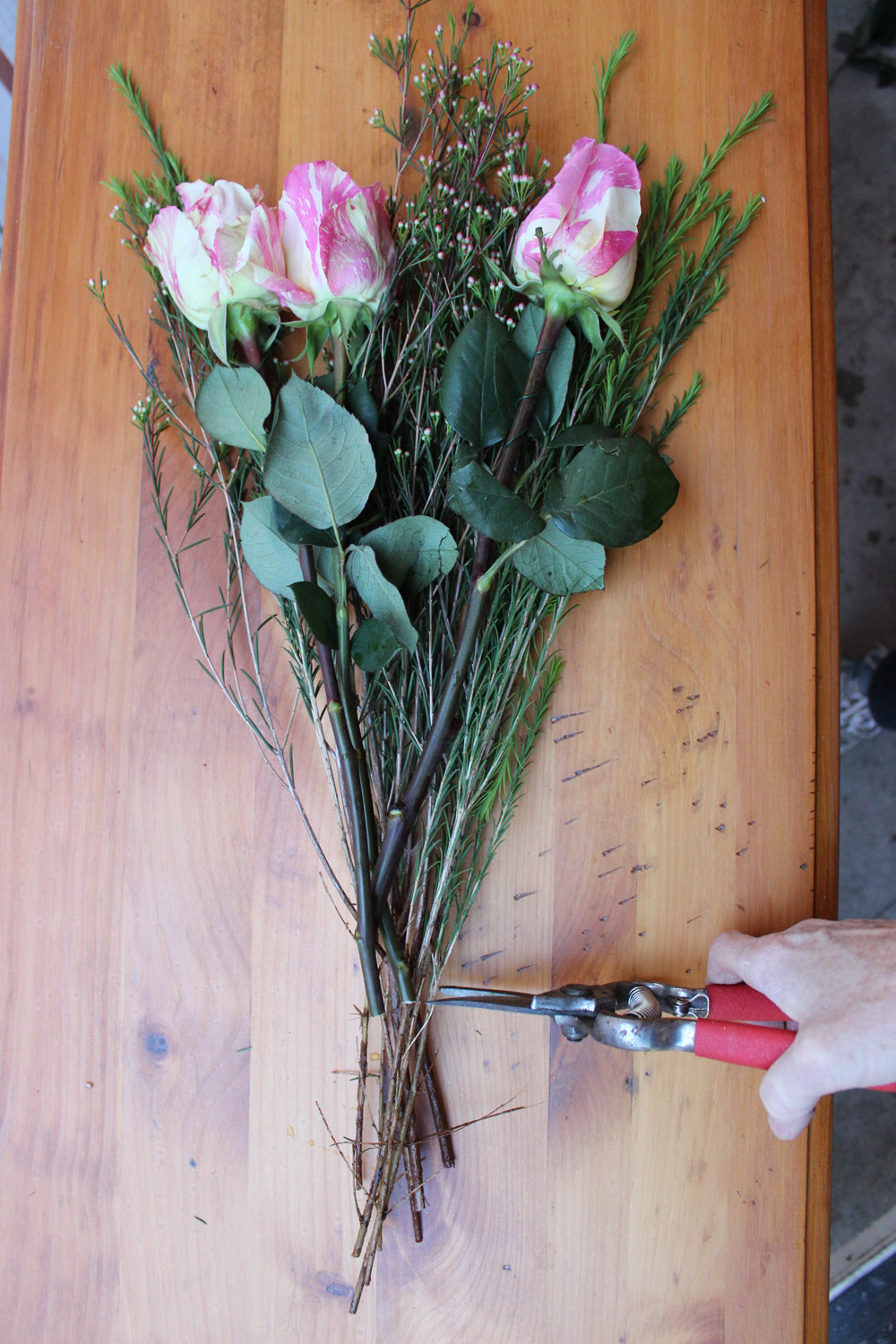 Make a grouping of 3 candy cane roses and some wax flower buds. Cut the wax flower bud stalks the same height as the roses. Place this grouping in the front of your vase.